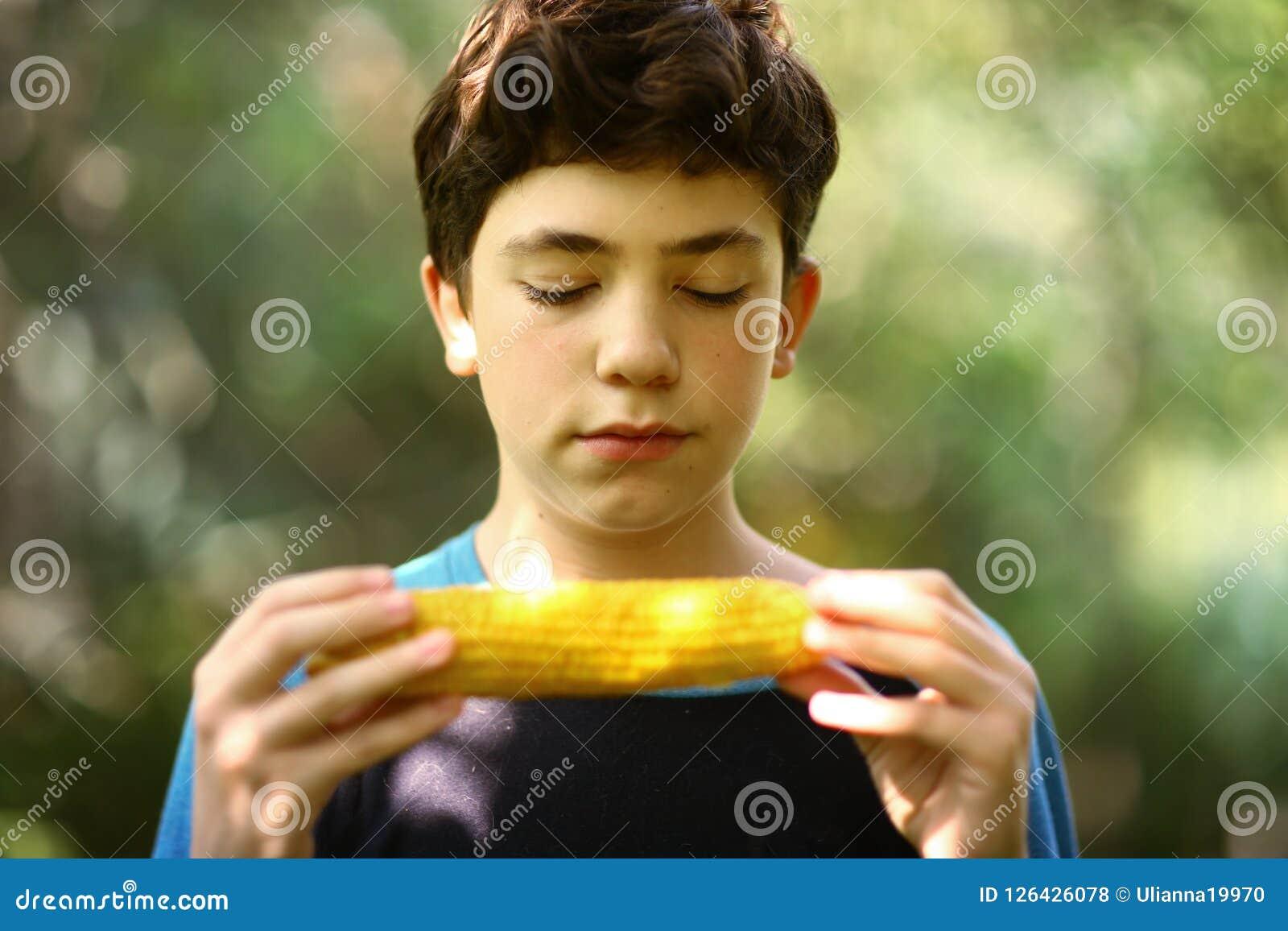 Fine bollita mangiare della pannocchia di granturco del ragazzo dell adolescente sulla foto