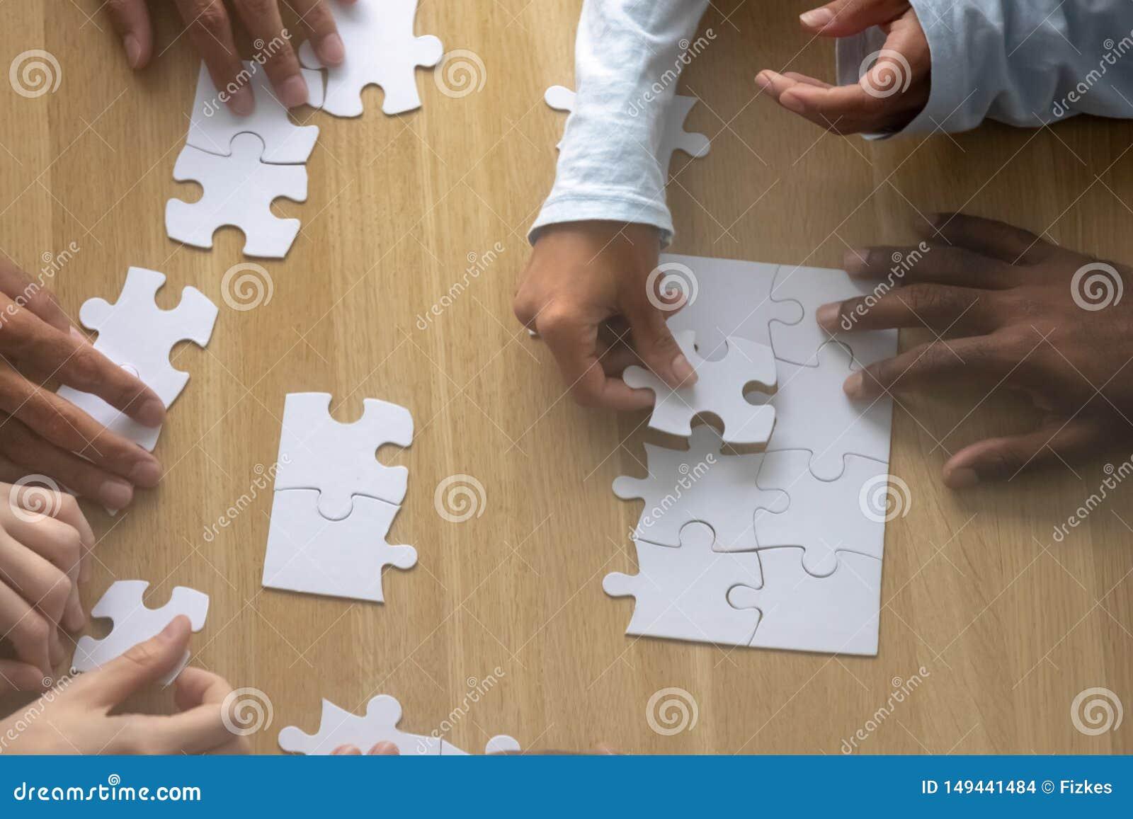 Fine di cui sopra superiore sulle mani umane multirazziali di vista che montano puzzle