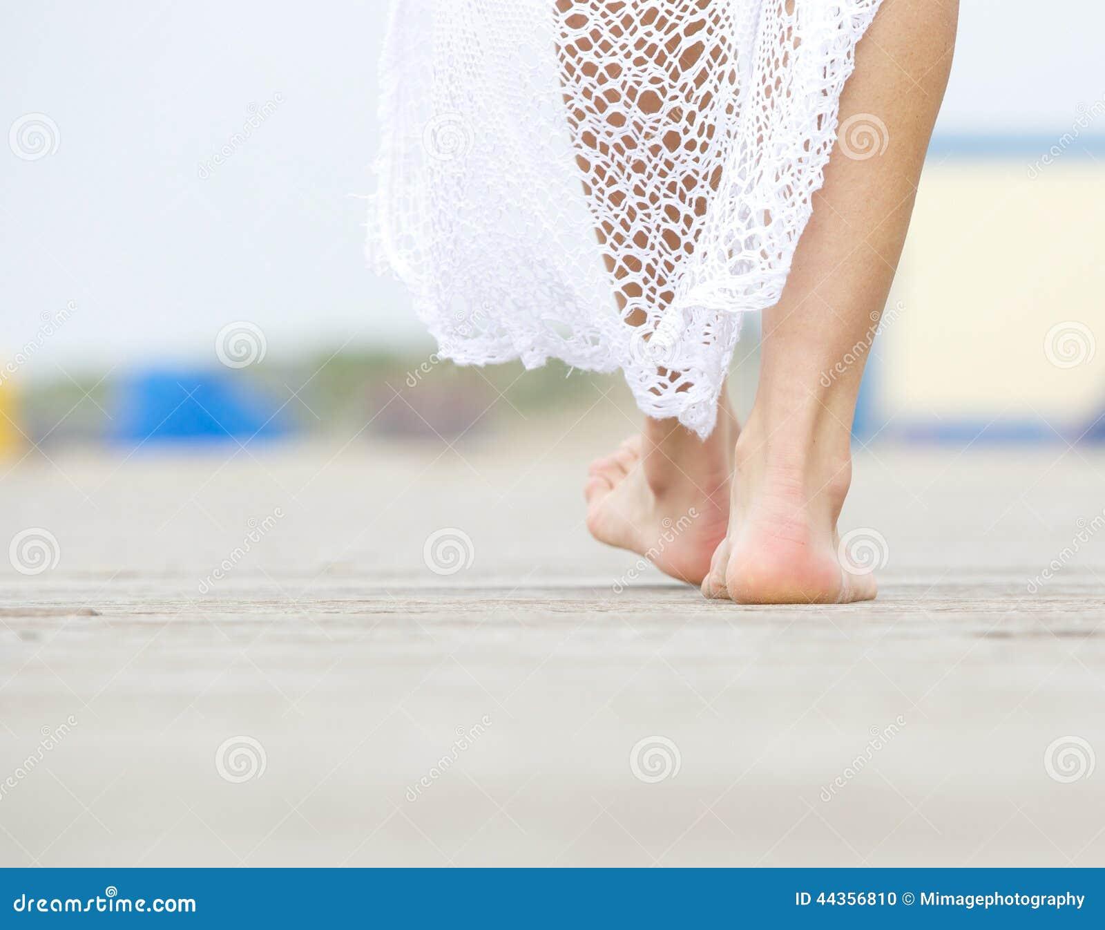 Fine di retrovisione sulla femmina che cammina a piedi nudi