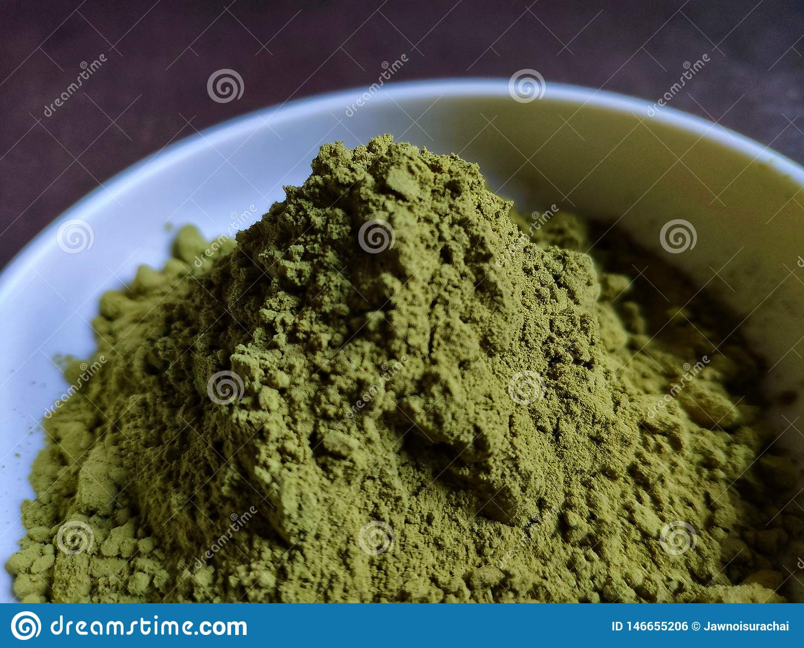 Green tea powder in the plate on the wooden table.