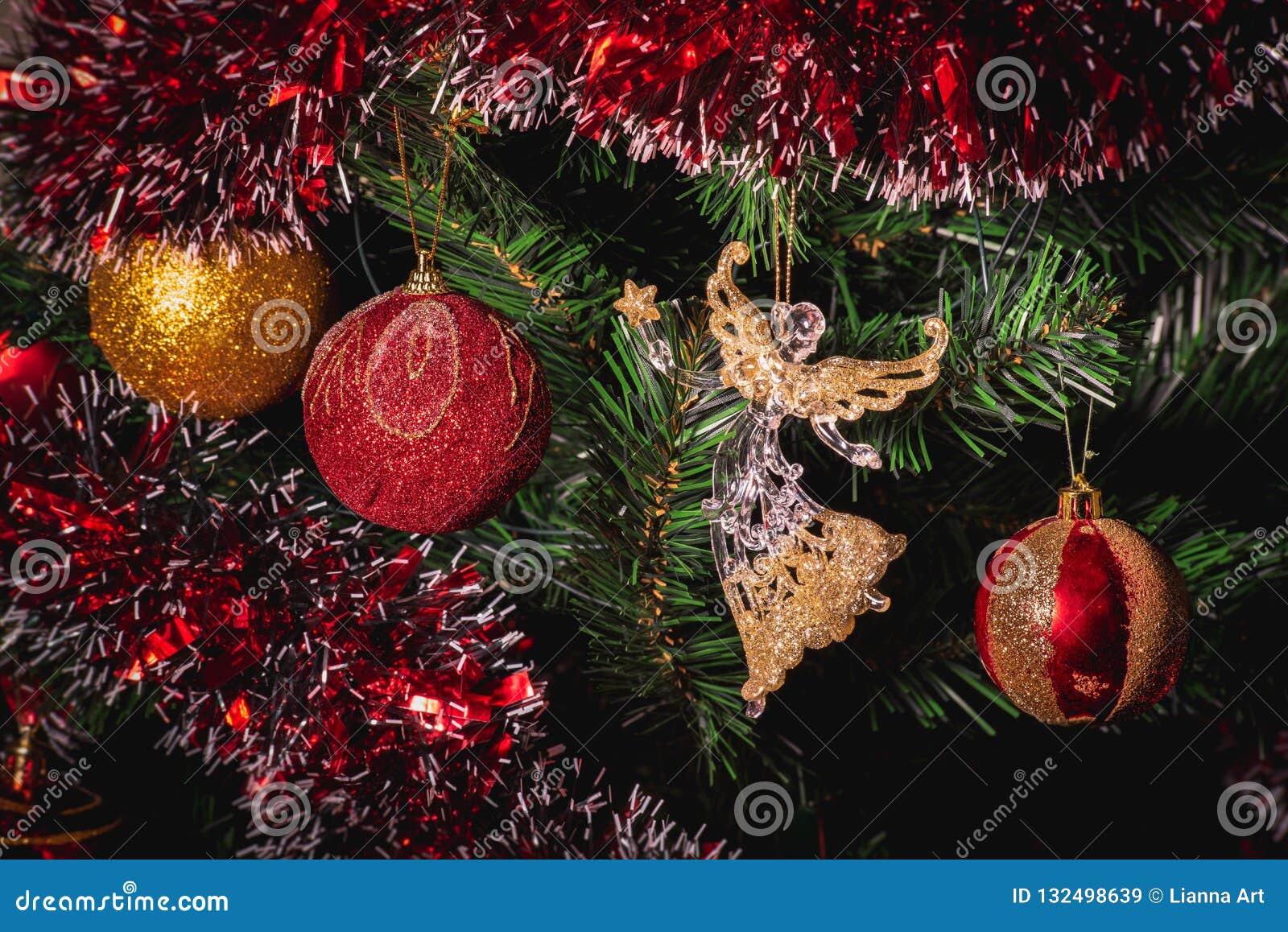 Fine su grande oro e su natale di vetro rosso del palla di scintillio e di angelo sull albero