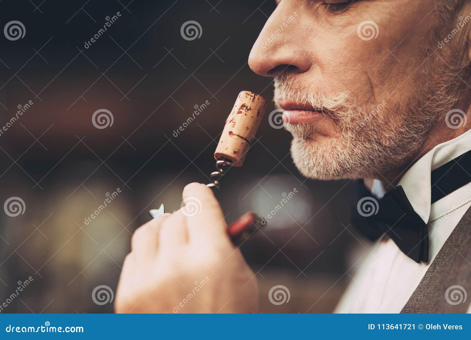 Fine in su Il sommelier con esperienza anziano odora il tappo del vino sulla cavaturaccioli, valutante il gusto della bevanda