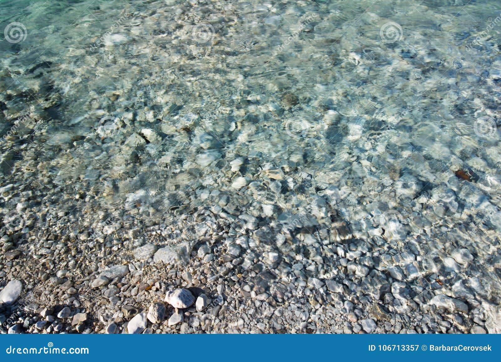 Fine su sulla riva della sponda del fiume con le pietre e la struttura cristallina del fondo del fiume del turchese puro