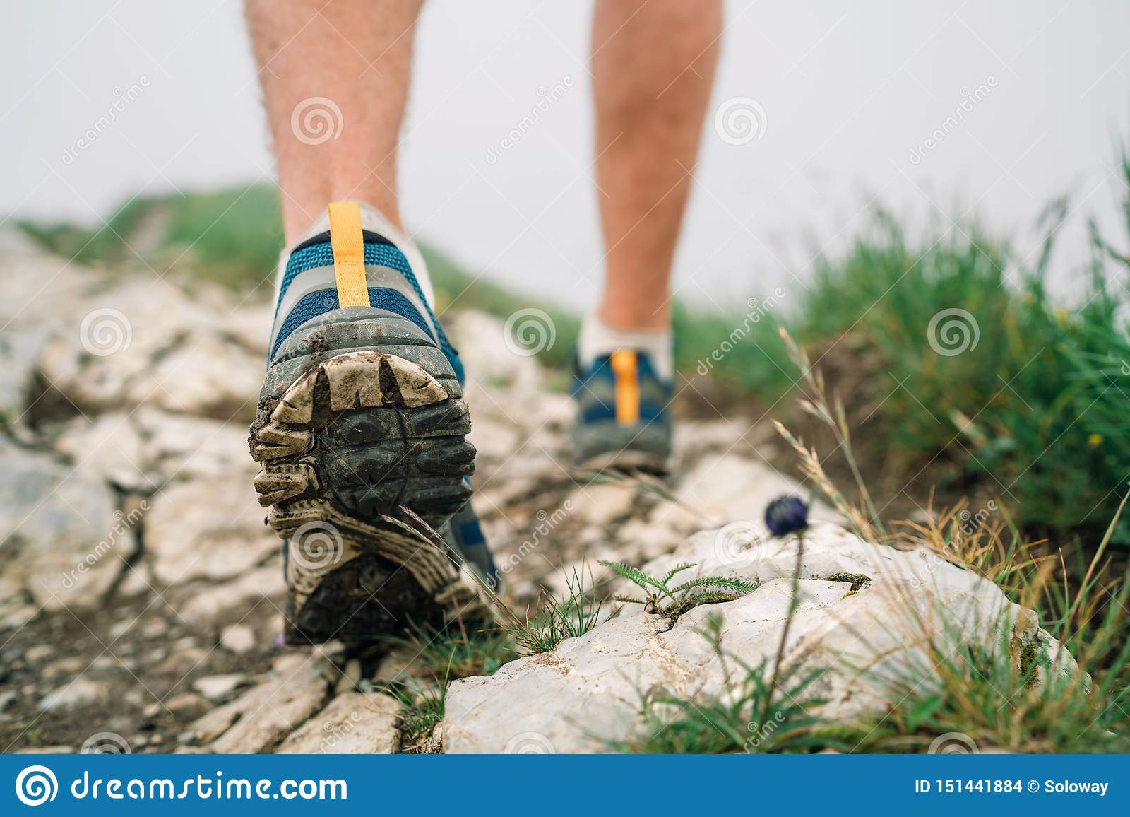 Fine sui piedi del viaggiatore di immagine negli stivali di trekking sul percorso roccioso della montagna ad ora legale