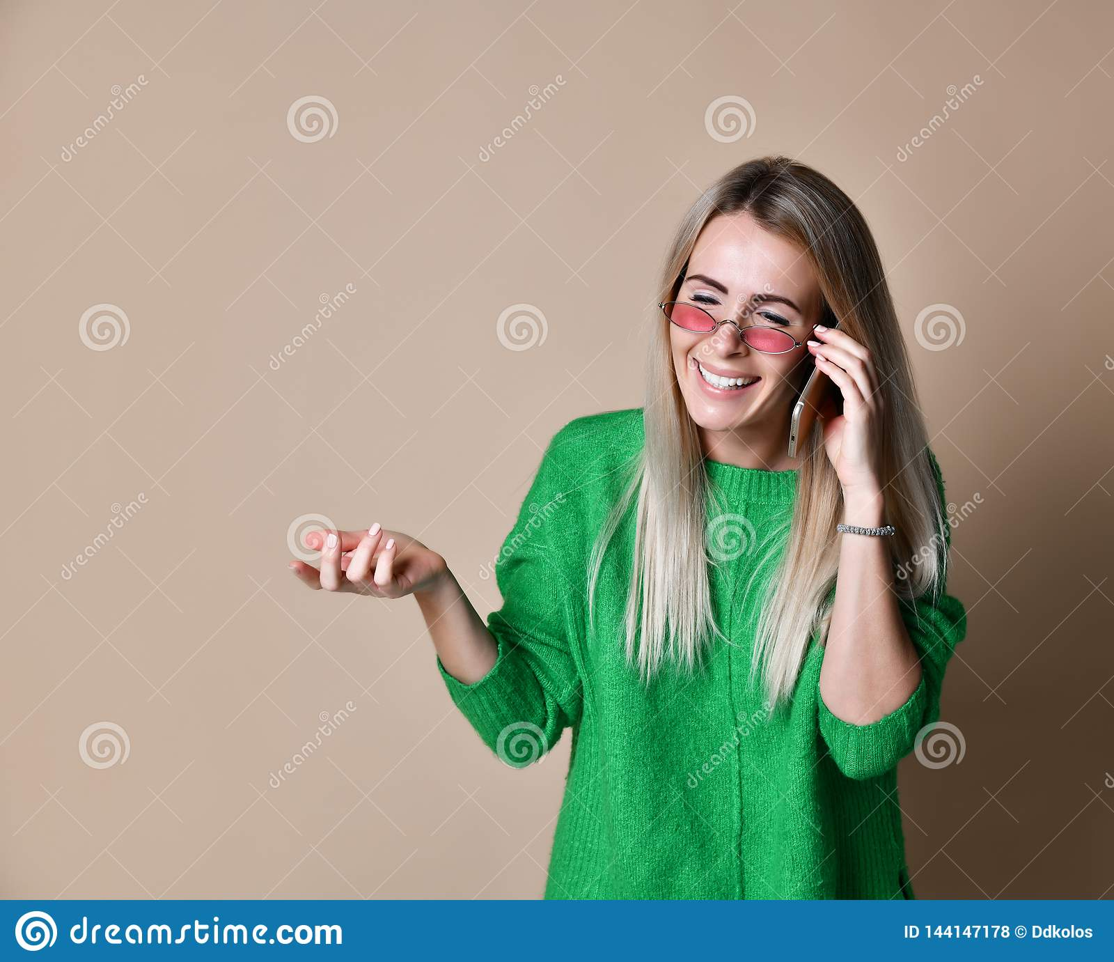 Fine sulla giovane donna bionda che parla con qualcuno sul suo telefono cellulare mentre esaminando la distanza con espressione f