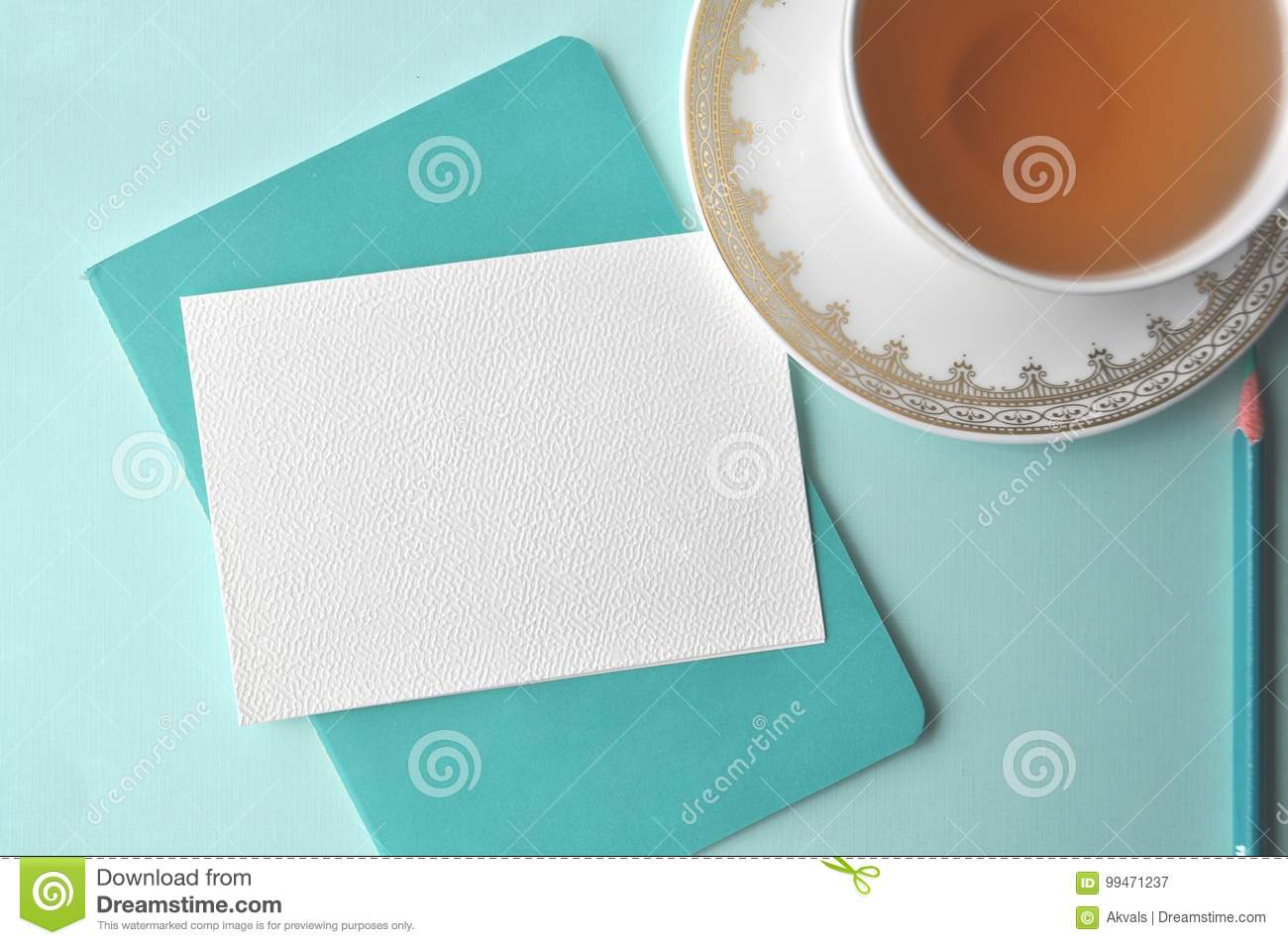 Fine white porcelain china cup with tea, teal pencil, white note card and aqua mint blue background