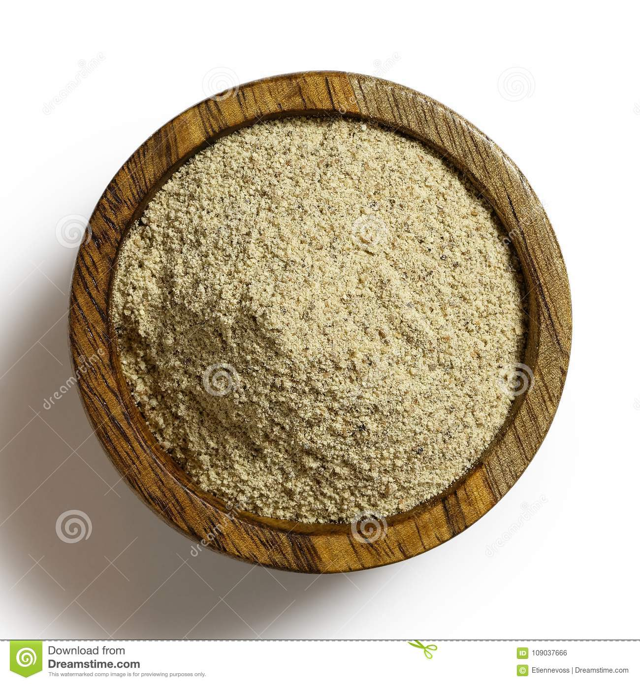 Finely ground white pepper in dark wood bowl isolated on white.