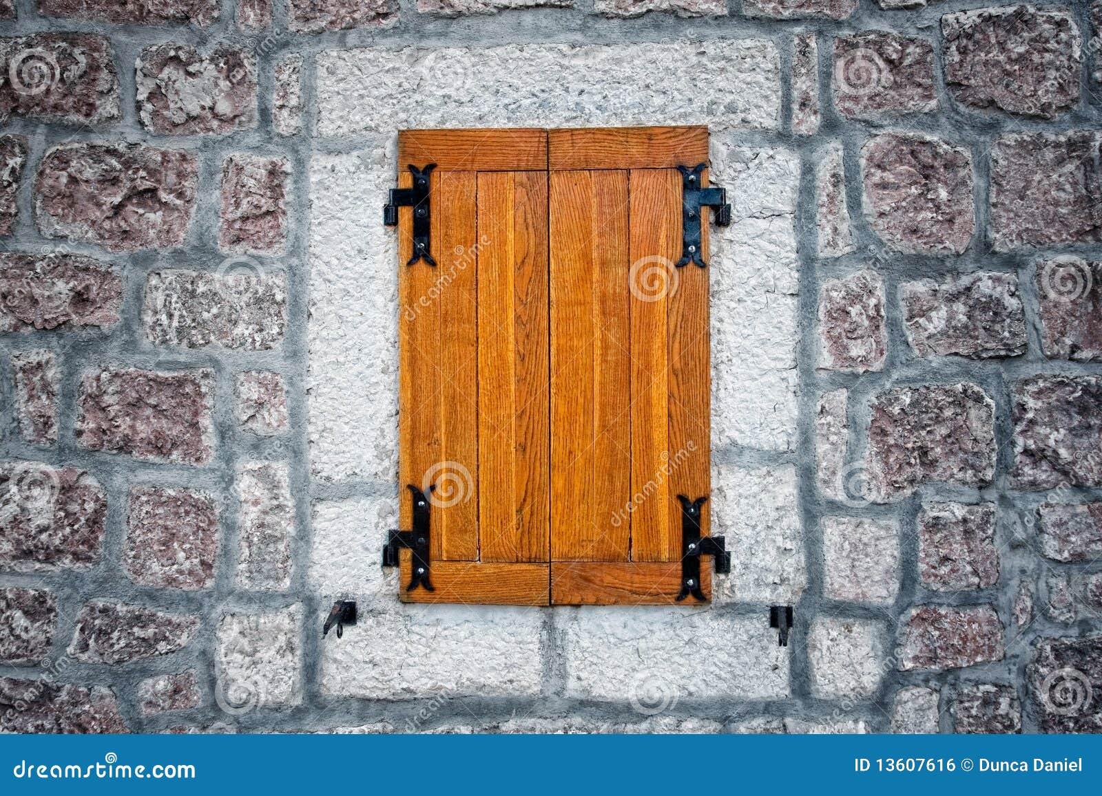 finestra antica rustica di legno e parete di pietra