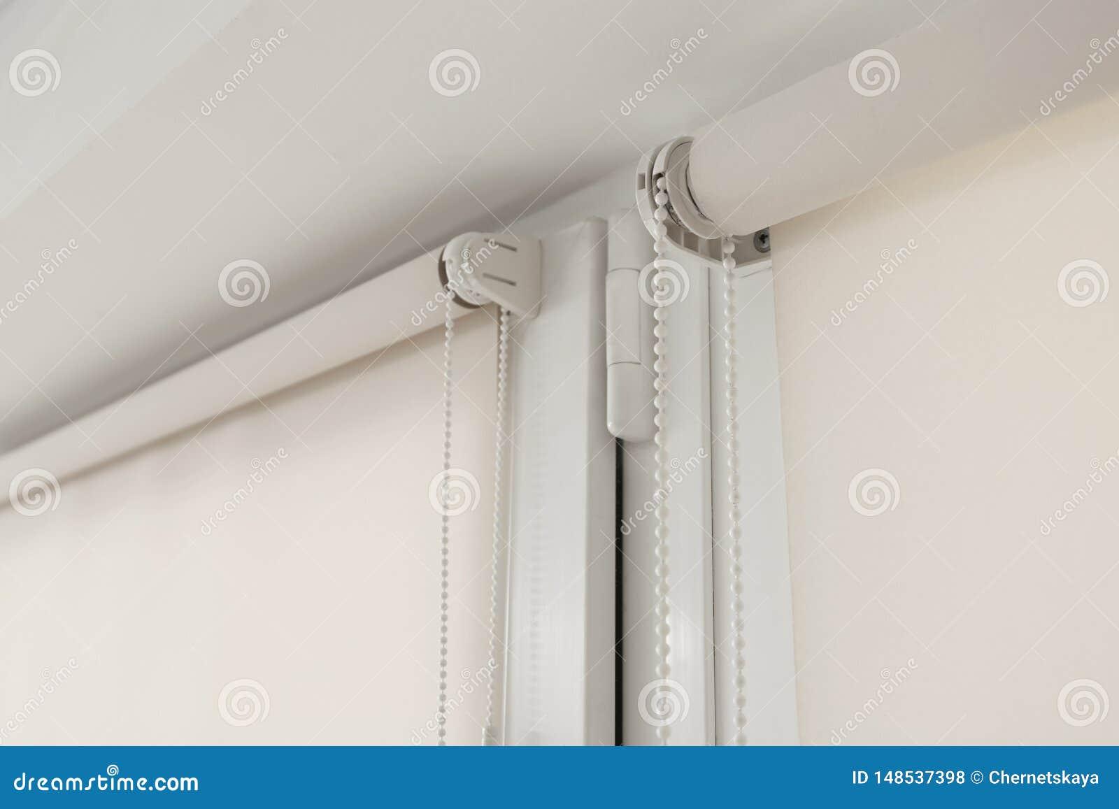 Finestra con i ciechi di rotolo moderni nella sala