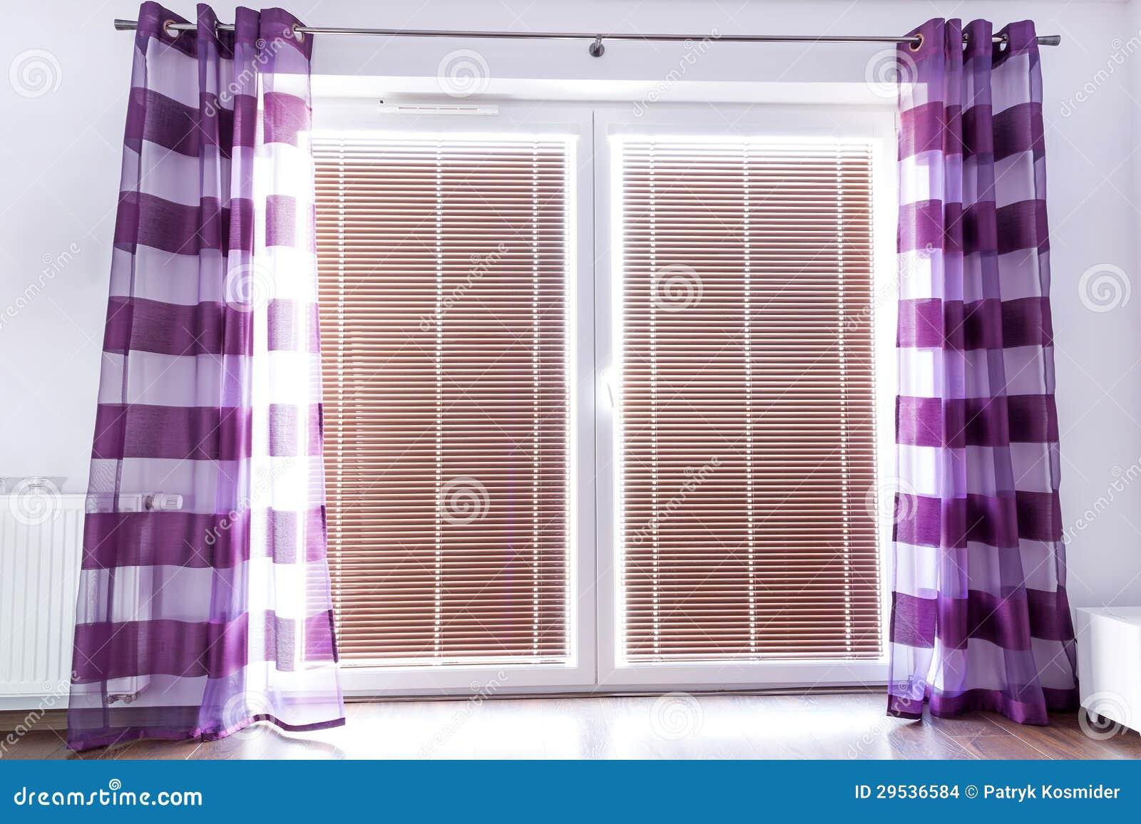 Finestra del balcone con le tende porpora fotografia stock