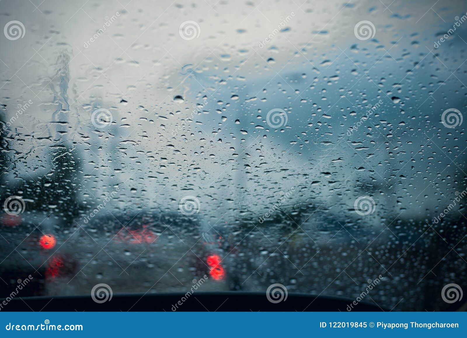 Finestra di automobile con le gocce di pioggia su vetro o sul parabrezza, traffico vago il giorno piovoso nella città