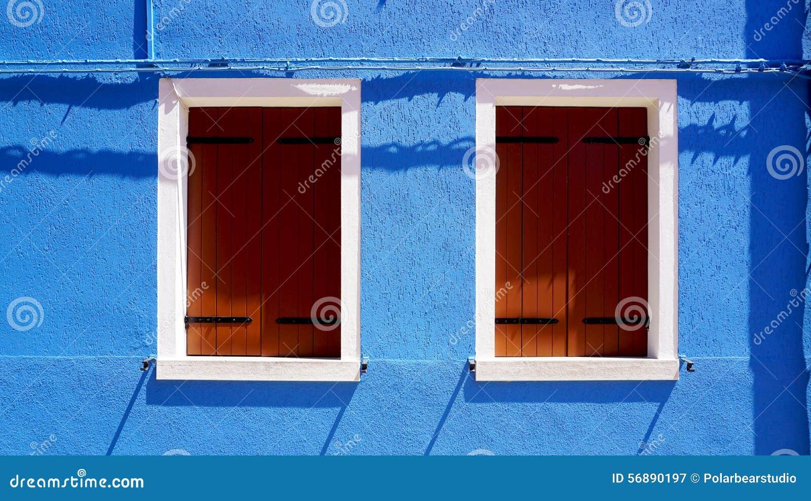 Finestra di legno con la struttura bianca sulla casa blu della parete di colore in Burano
