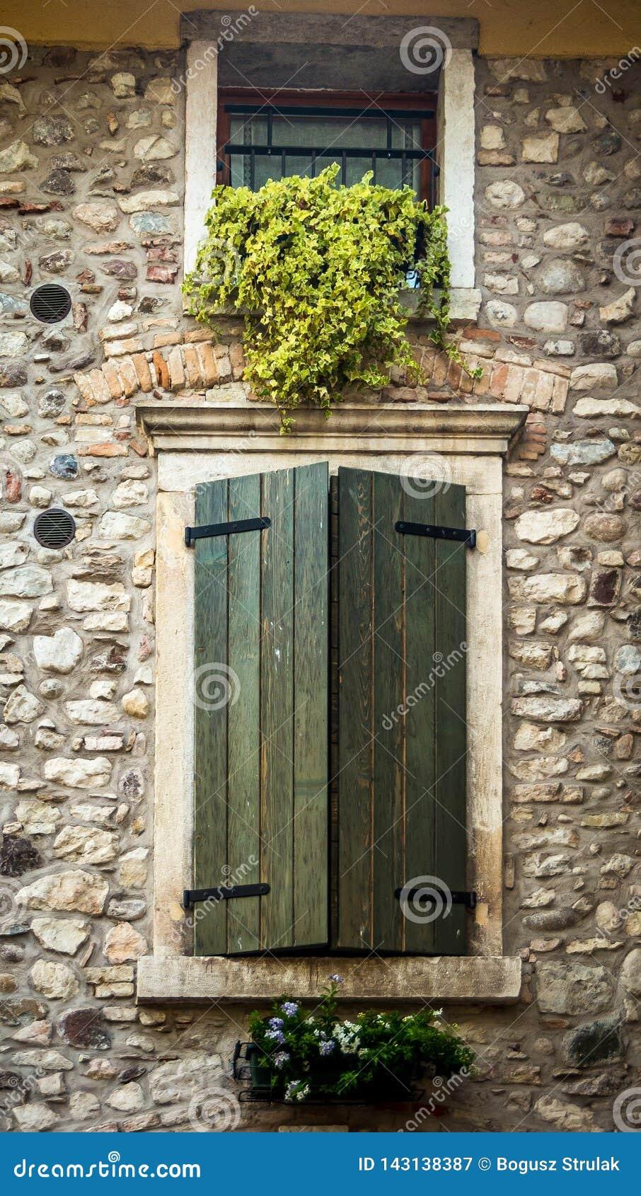 Finestra dietro gli otturatori di legno in Toscana, Italia