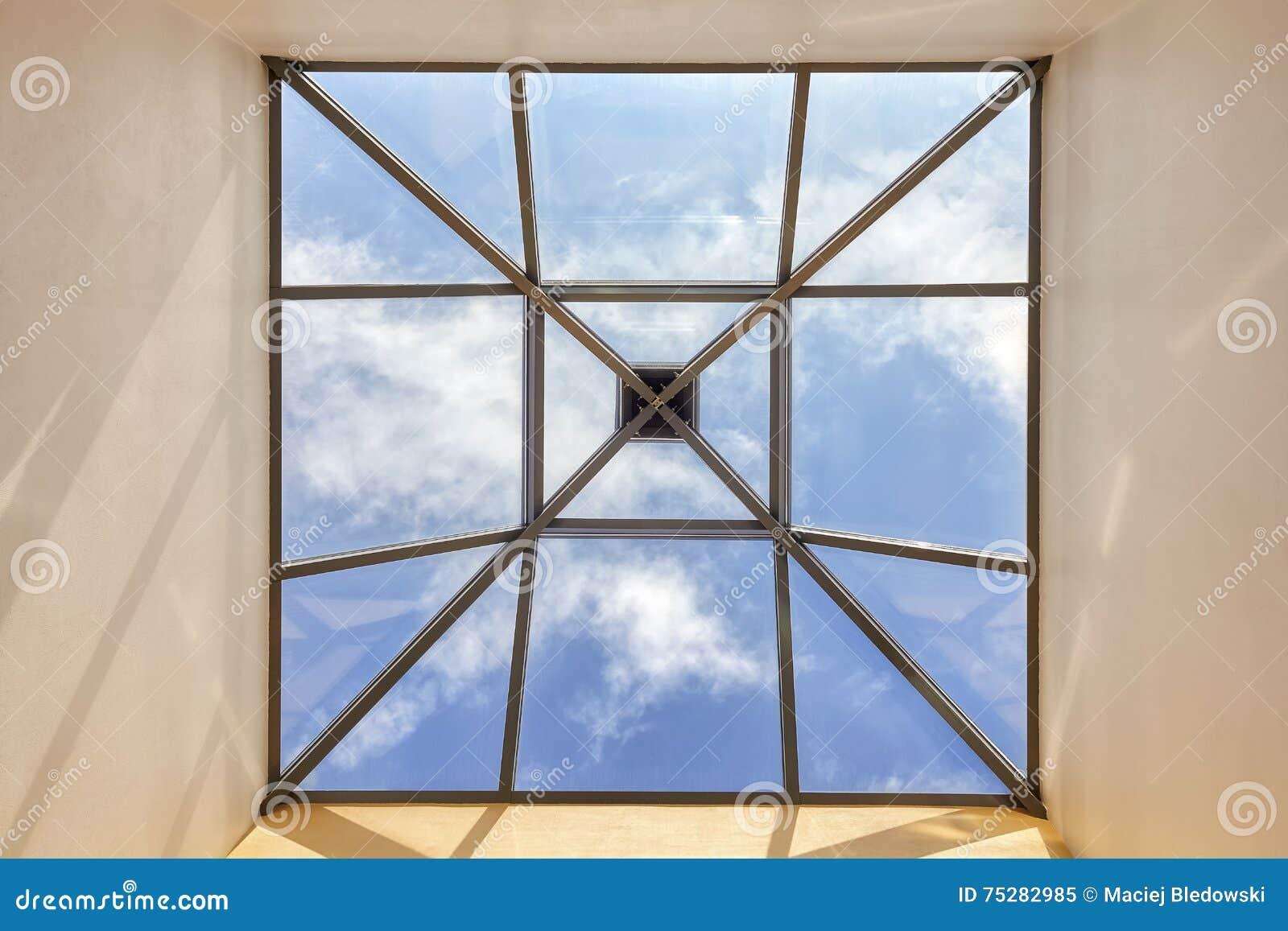 finestra in un soffitto con cielo blu immagine stock