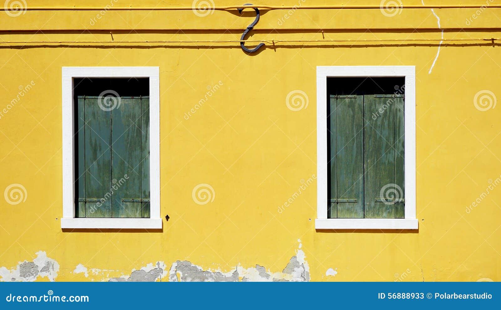 Finestra verde del woodem sulla parete gialla