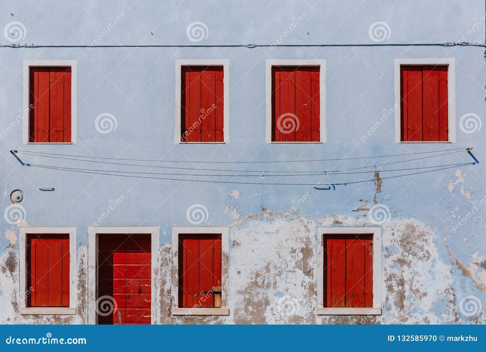 Finestre e porta di legno rosse sulla vecchia parete blu-chiaro, sul islan