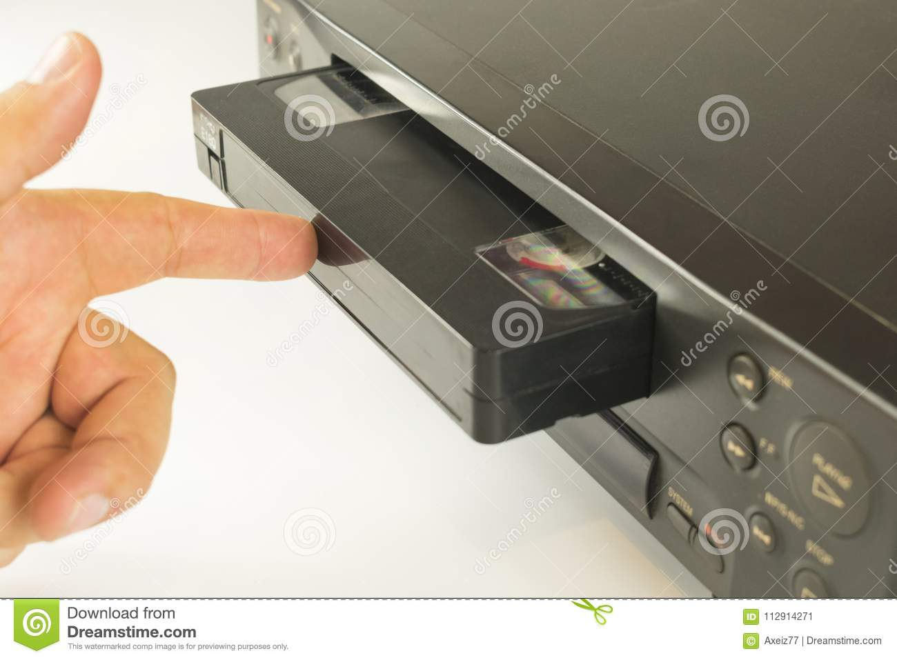 Finger Pushing A Video Cassette Into The Inside Of VCR For Viewing Recordings On White Background