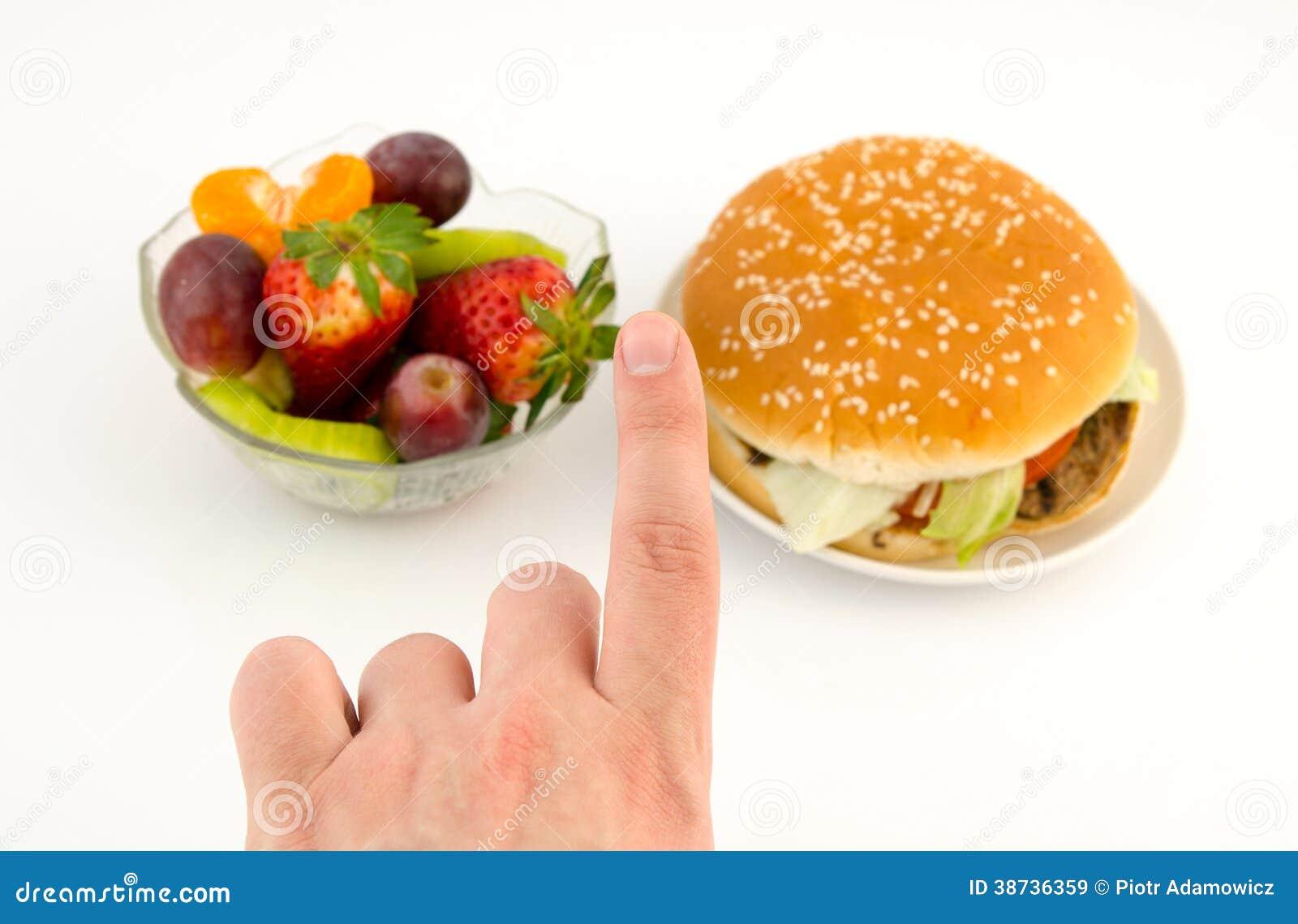 Finger som väljer mellan hamburgaren och frukter.