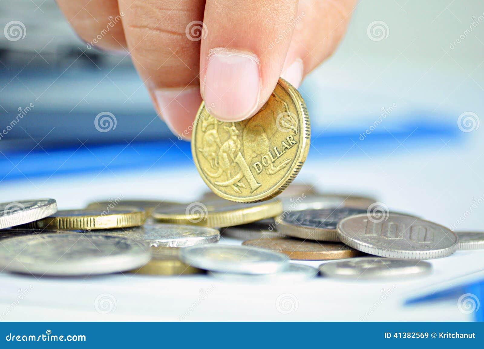 Fingrar som upp väljer ett mynt - en australisk dollar (AUD)