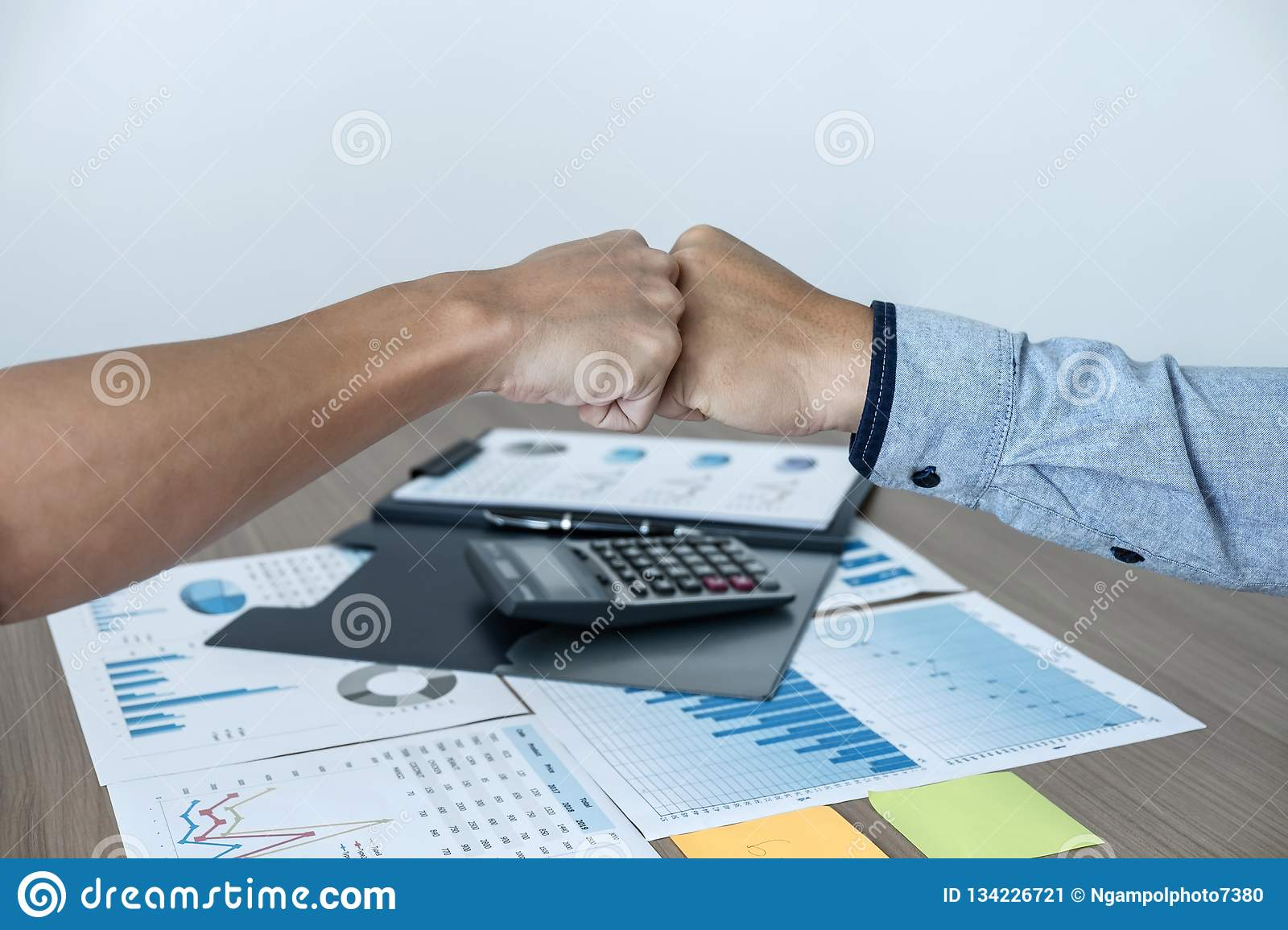 Finishing up a meeting, giving first bump of hand`s two happy business people after contract agreement to become a partner,