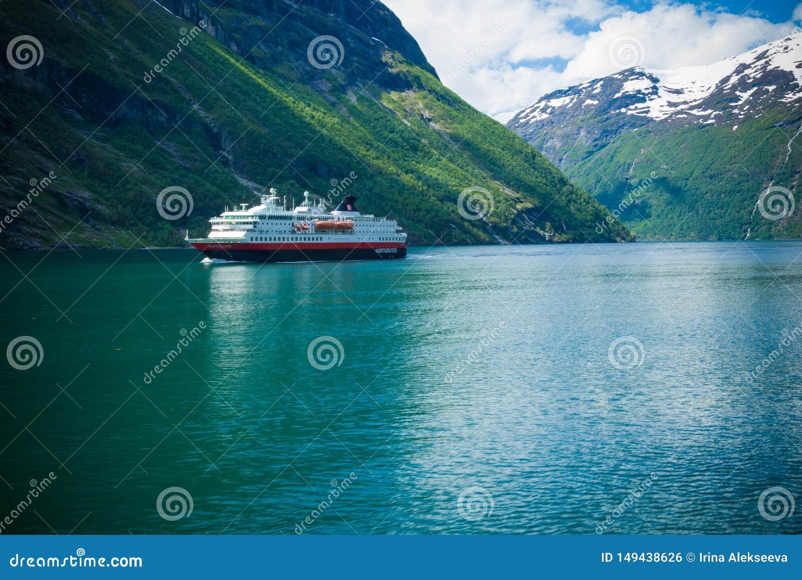 Fiorde de Geiranger, Noruega-JUNHO 15,2012: a balsa Hurtigruten do cruzeiro navega ao longo de Geirangerfjord A viagem foi descri