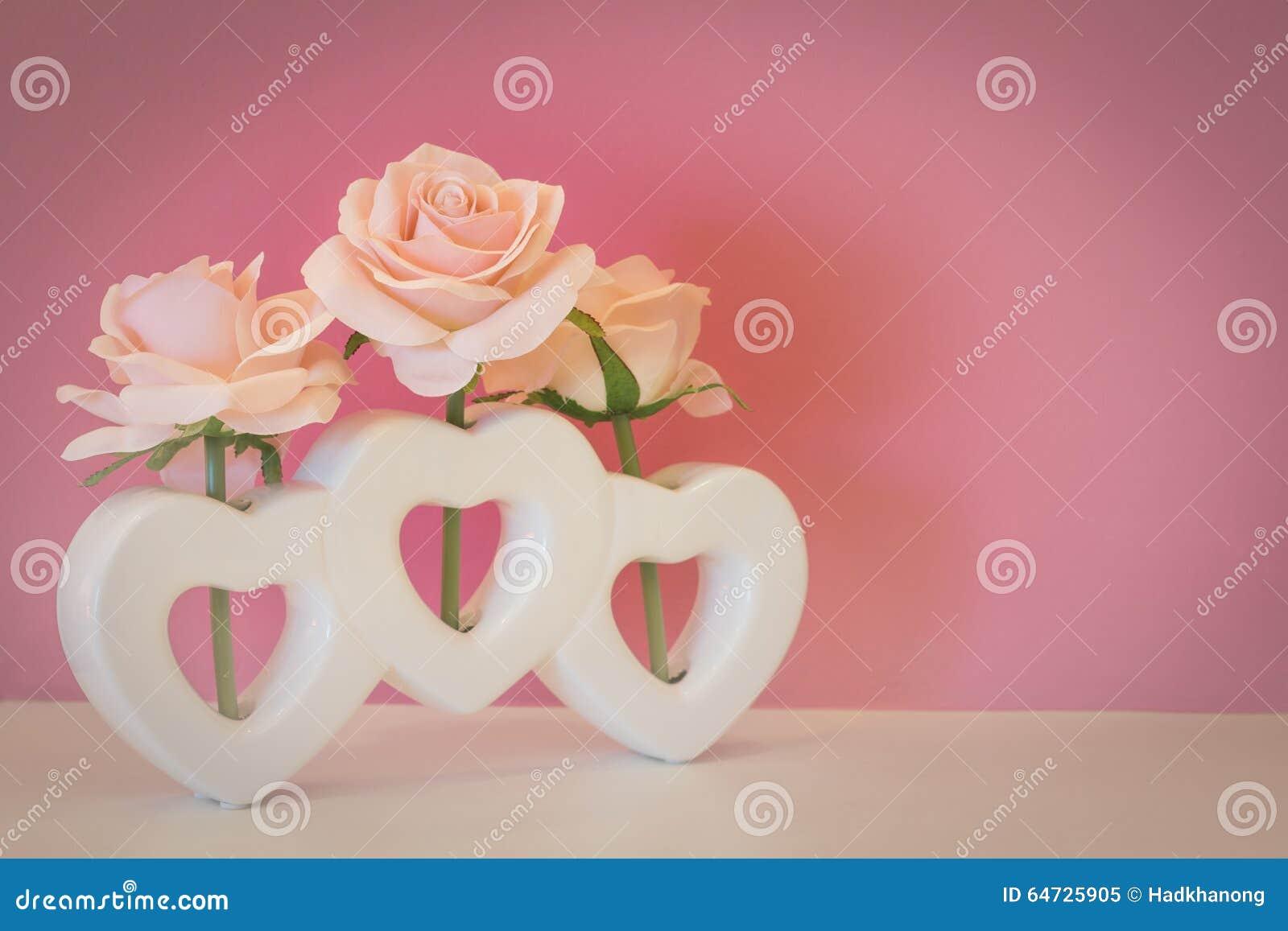 Fiore artificiale della rosa di rosa in vaso di forma del cuore