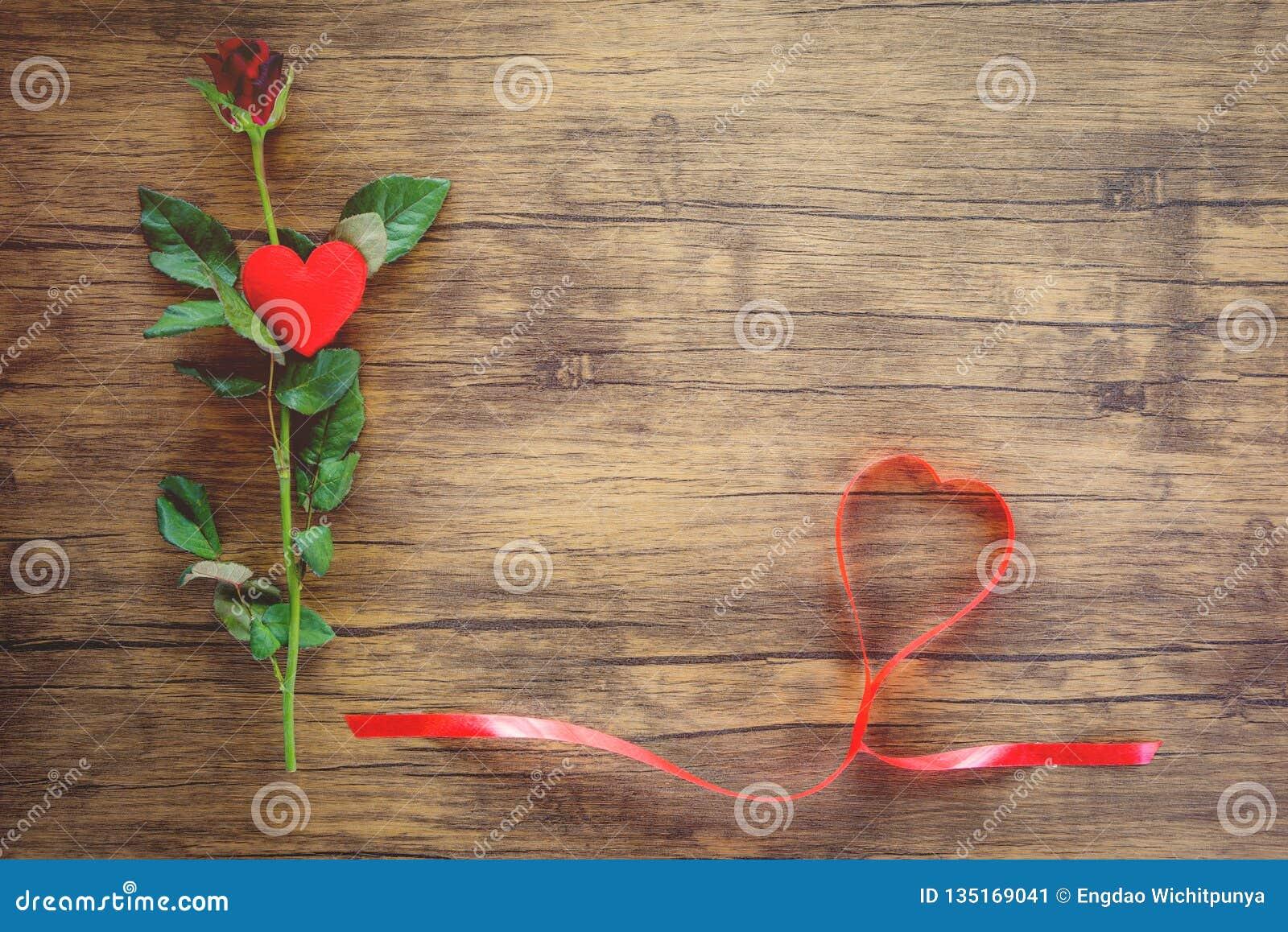 Fiore della rosa rossa di giorno di biglietti di S. Valentino su cuore rosso di legno con le rose e sul cuore rosso del nastro su