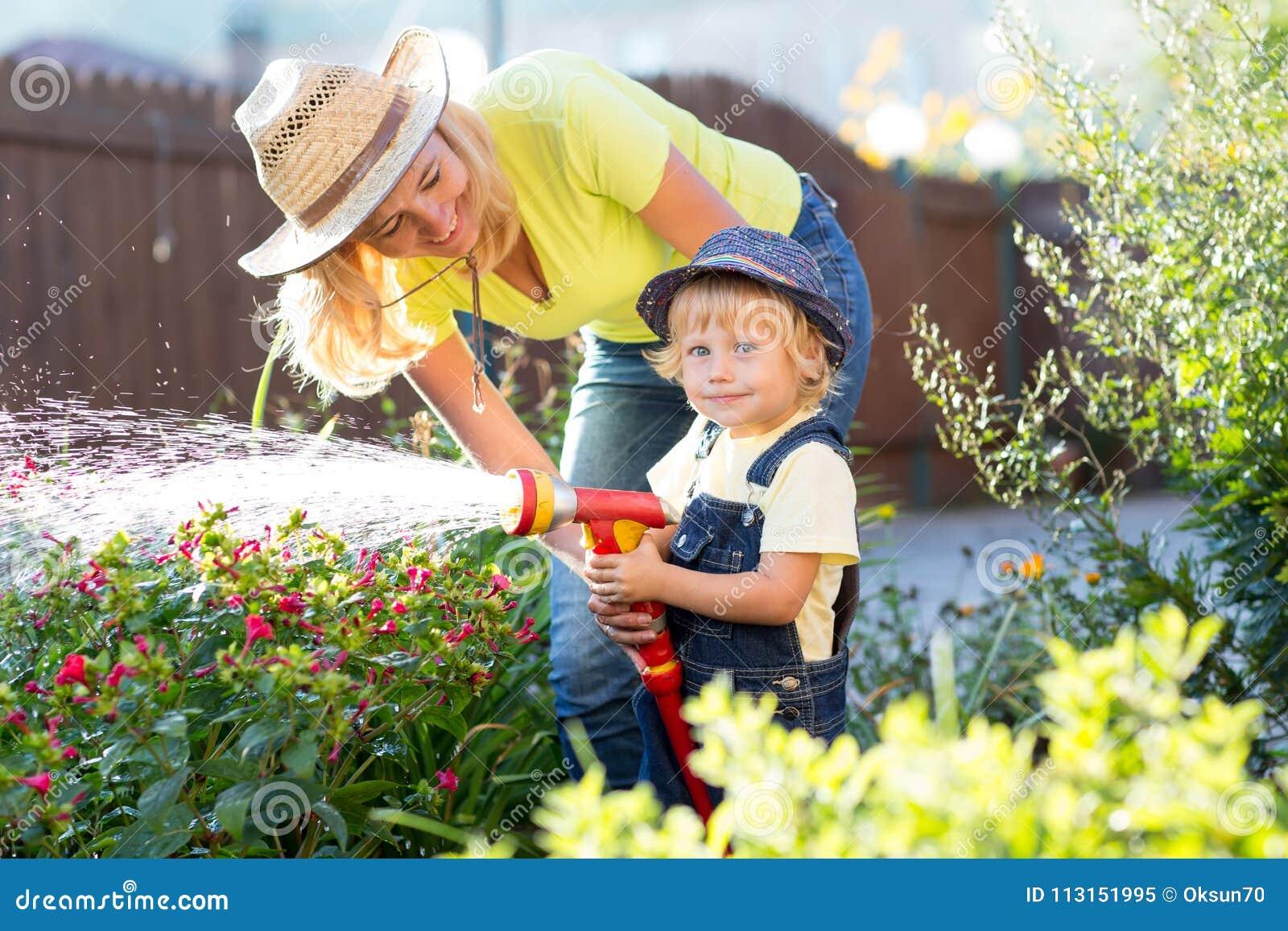 Fiori d innaffiatura figlio del piccolo e della mamma in giardino