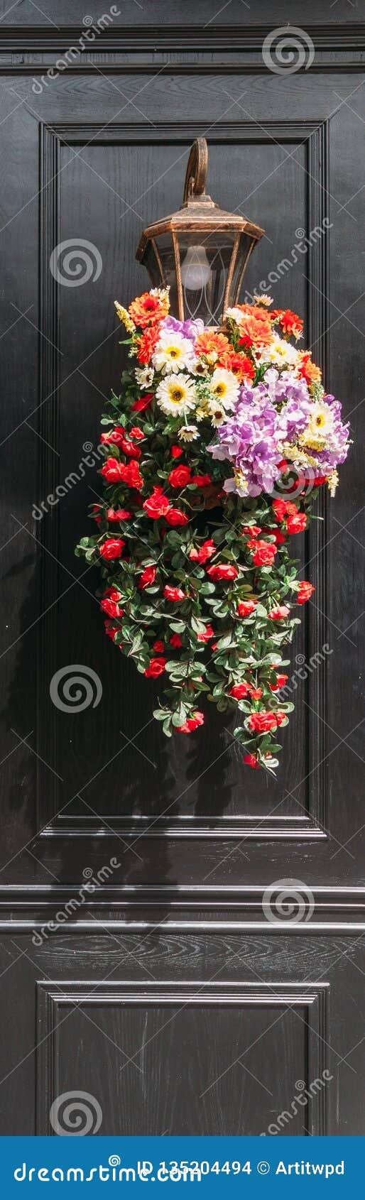 Fiori decorati sulla lampada con la parete di legno dipinta nera nel fondo