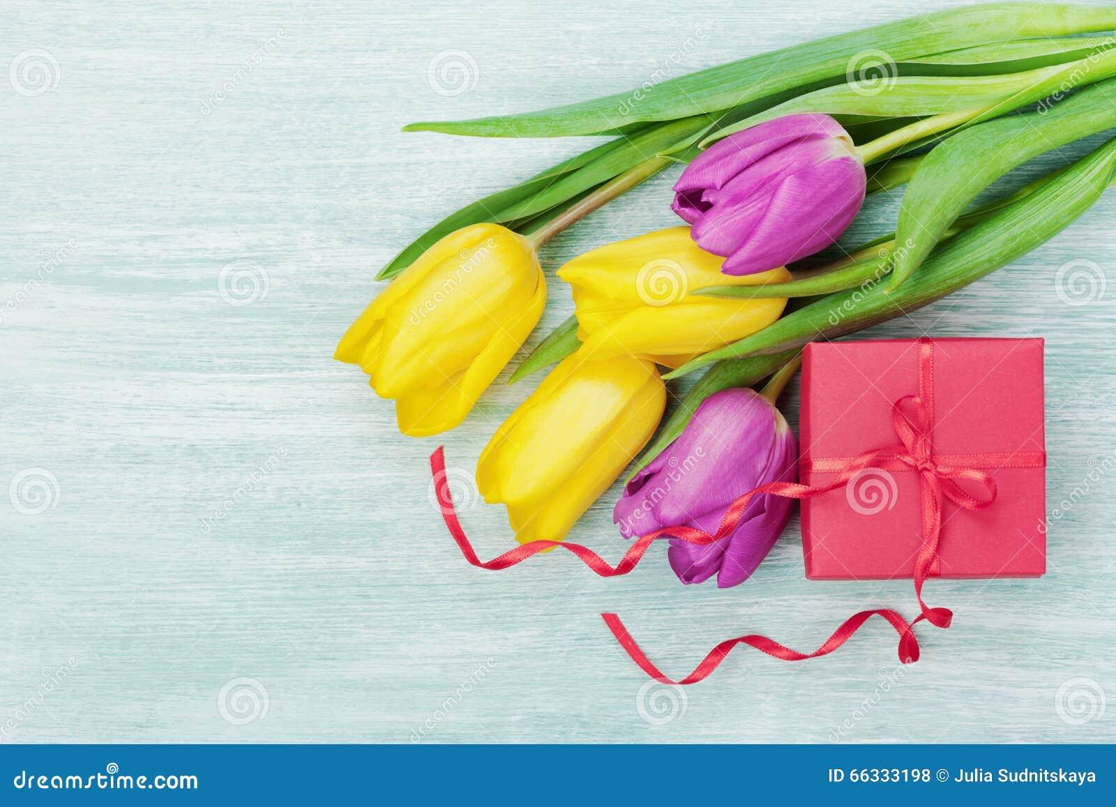 Fiori del contenitore e del tulipano di regalo sulla tavola rustica per il giorno dell 8 marzo, di Giornata internazionale della