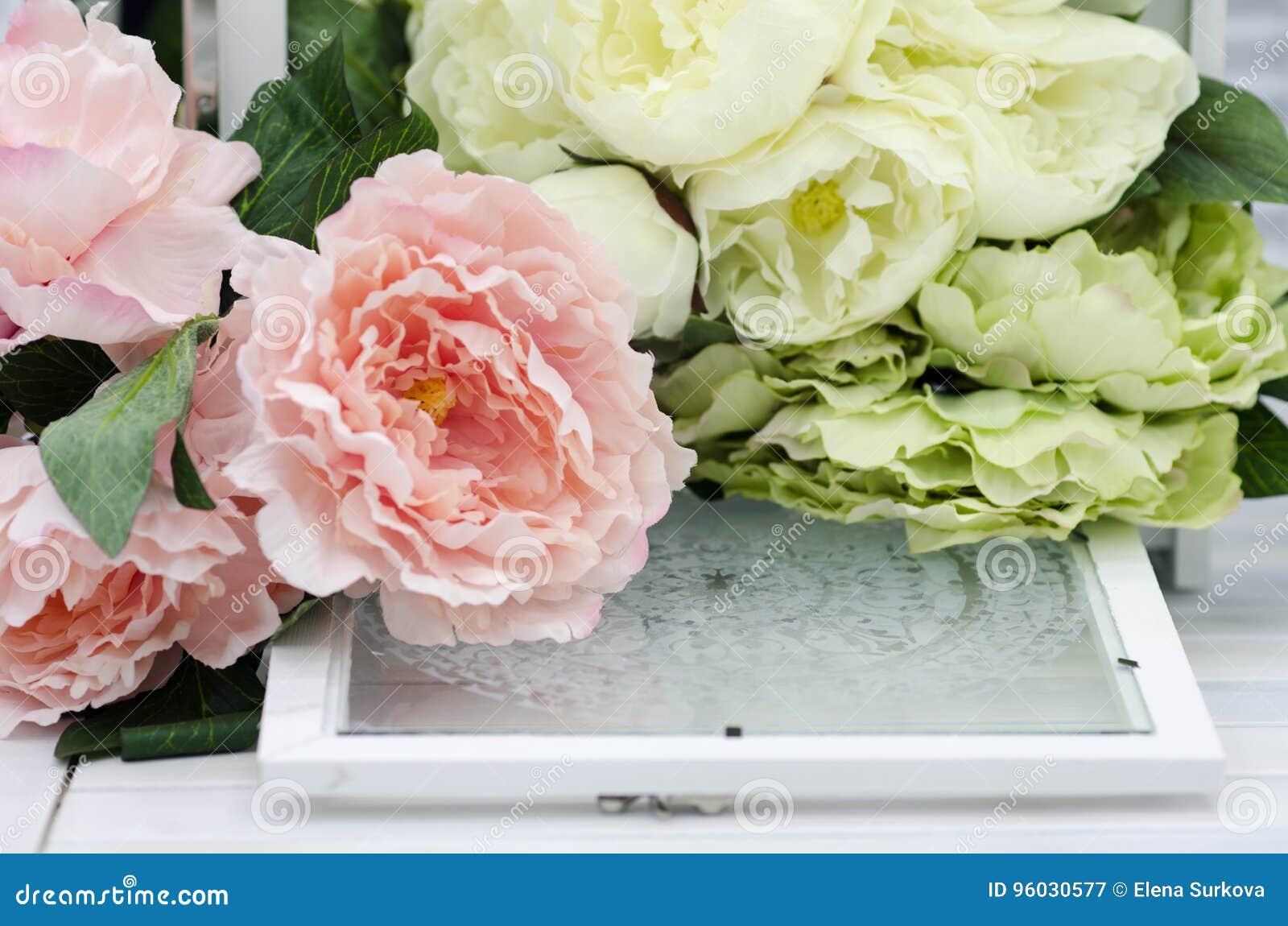 Fiori e lampade sulla tavola di legno bianca