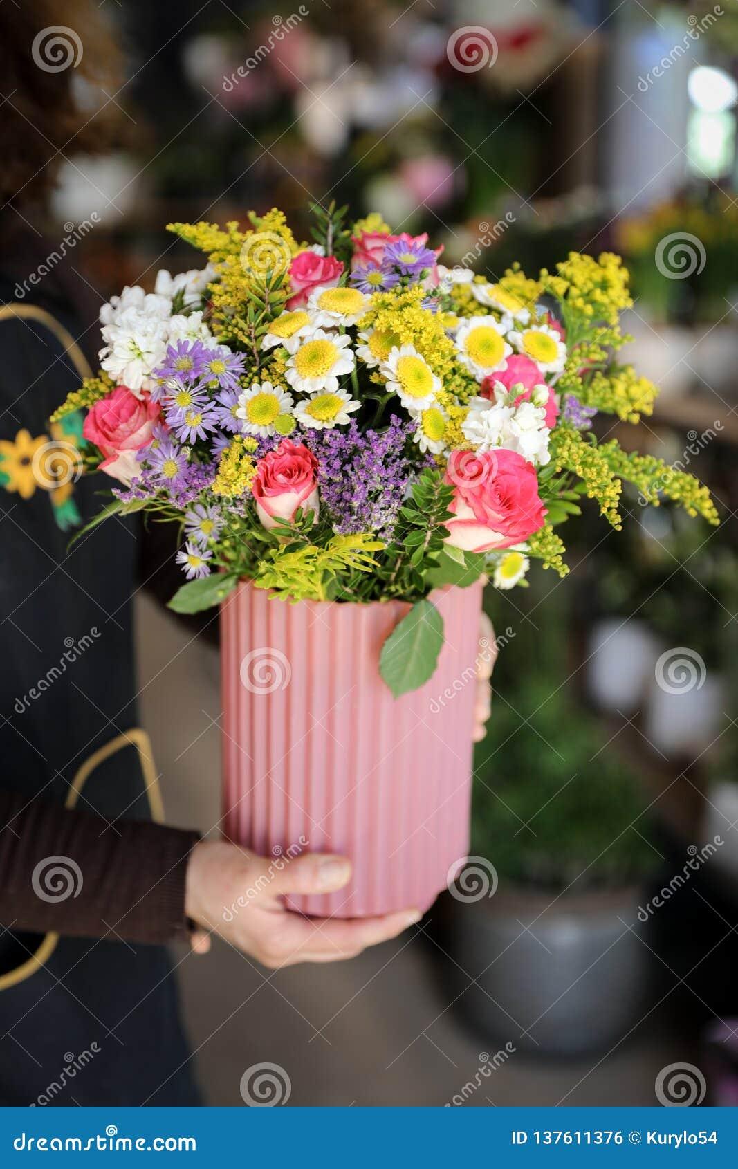 Fiorista che tiene un vaso con bella disposizione dei fiori delle rose rosa, degli aster lilla, dei crisantemi bianchi e di altre