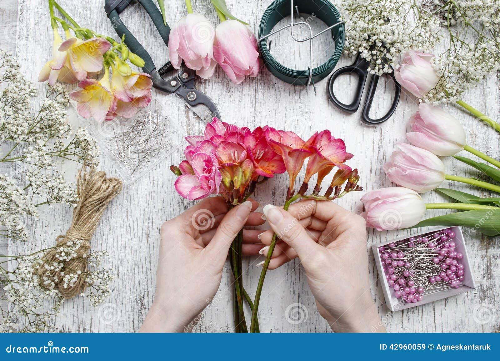 Fiorista sul lavoro Donna che fa mazzo dei fiori di fresia della molla
