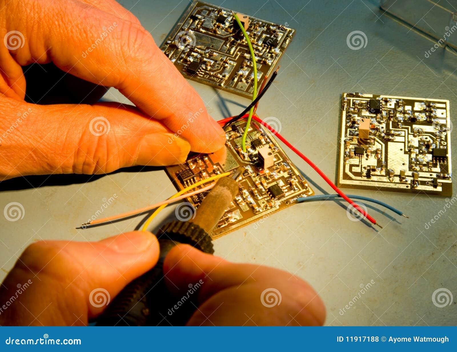 Fios de solda do coordenador a uma placa de circuito.