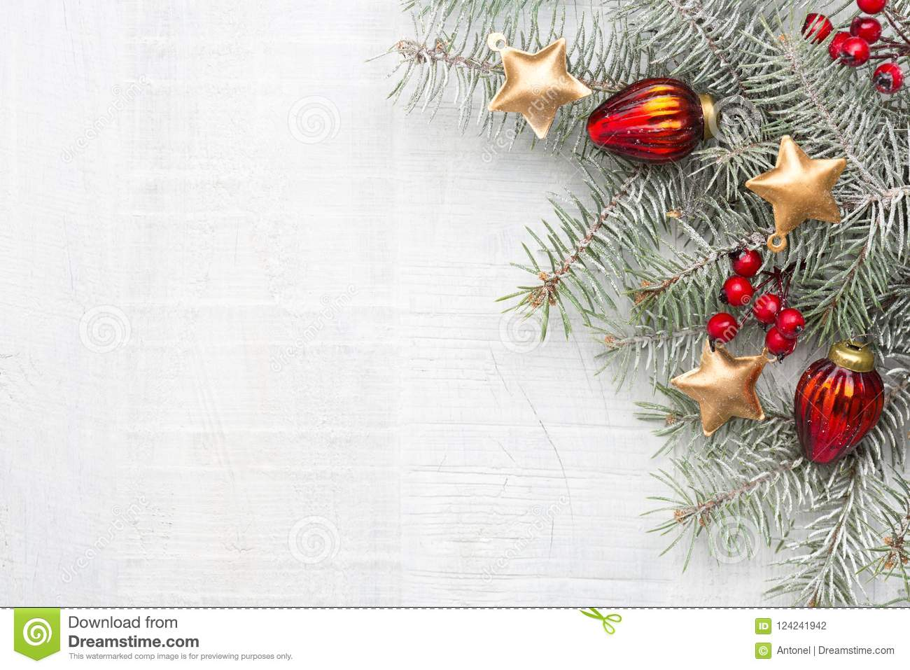 Fir branch with Christmas decorations on white rustic wooden background with copy space for text