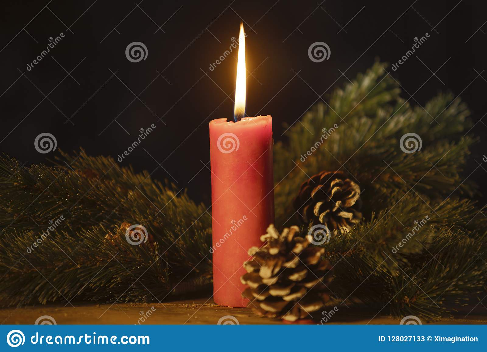Fir tree branches with burning candle on table