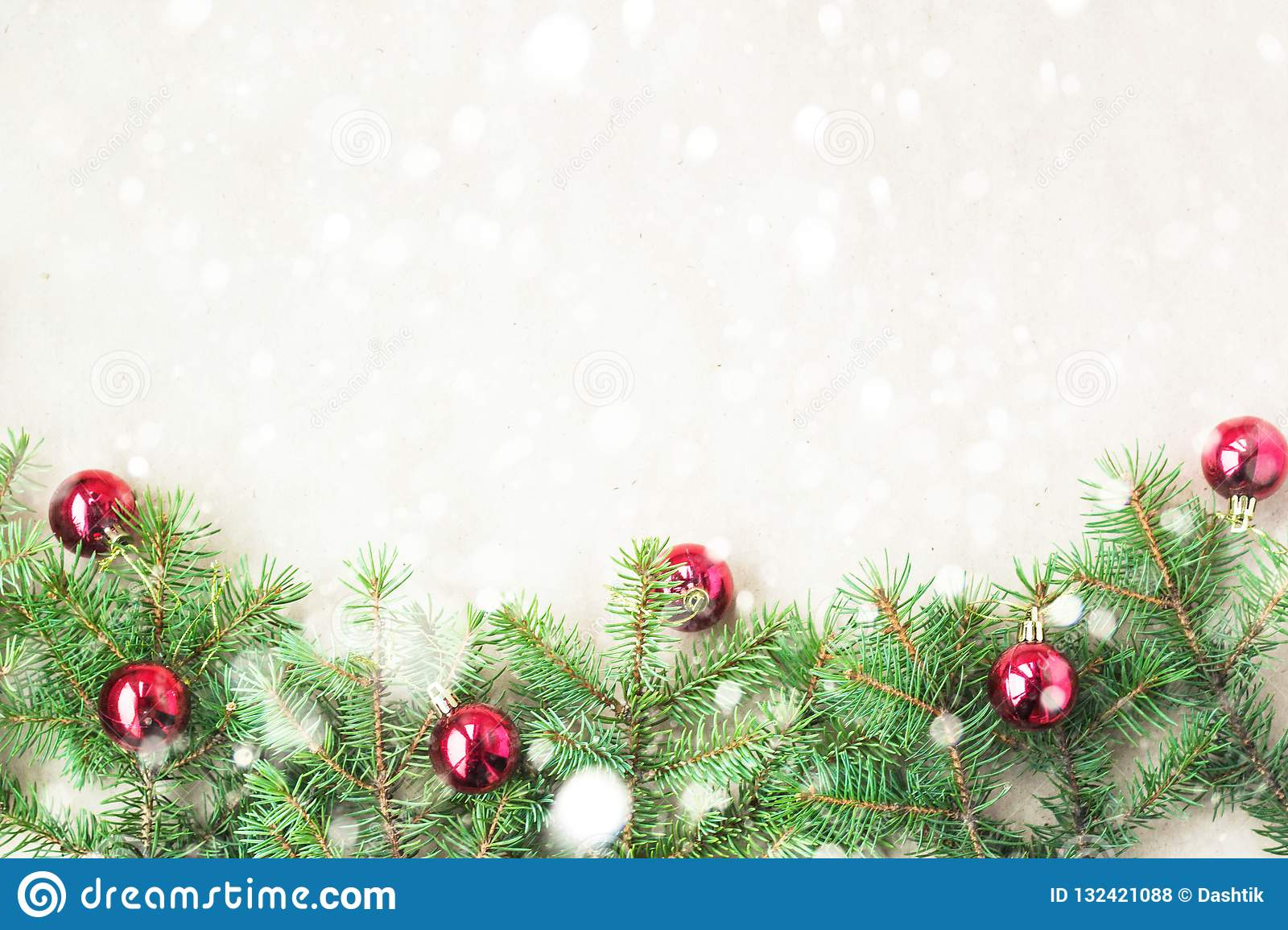 Fir tree branches decorated with red christmas balls as border on a rustic holiday background frame with snow copy space
