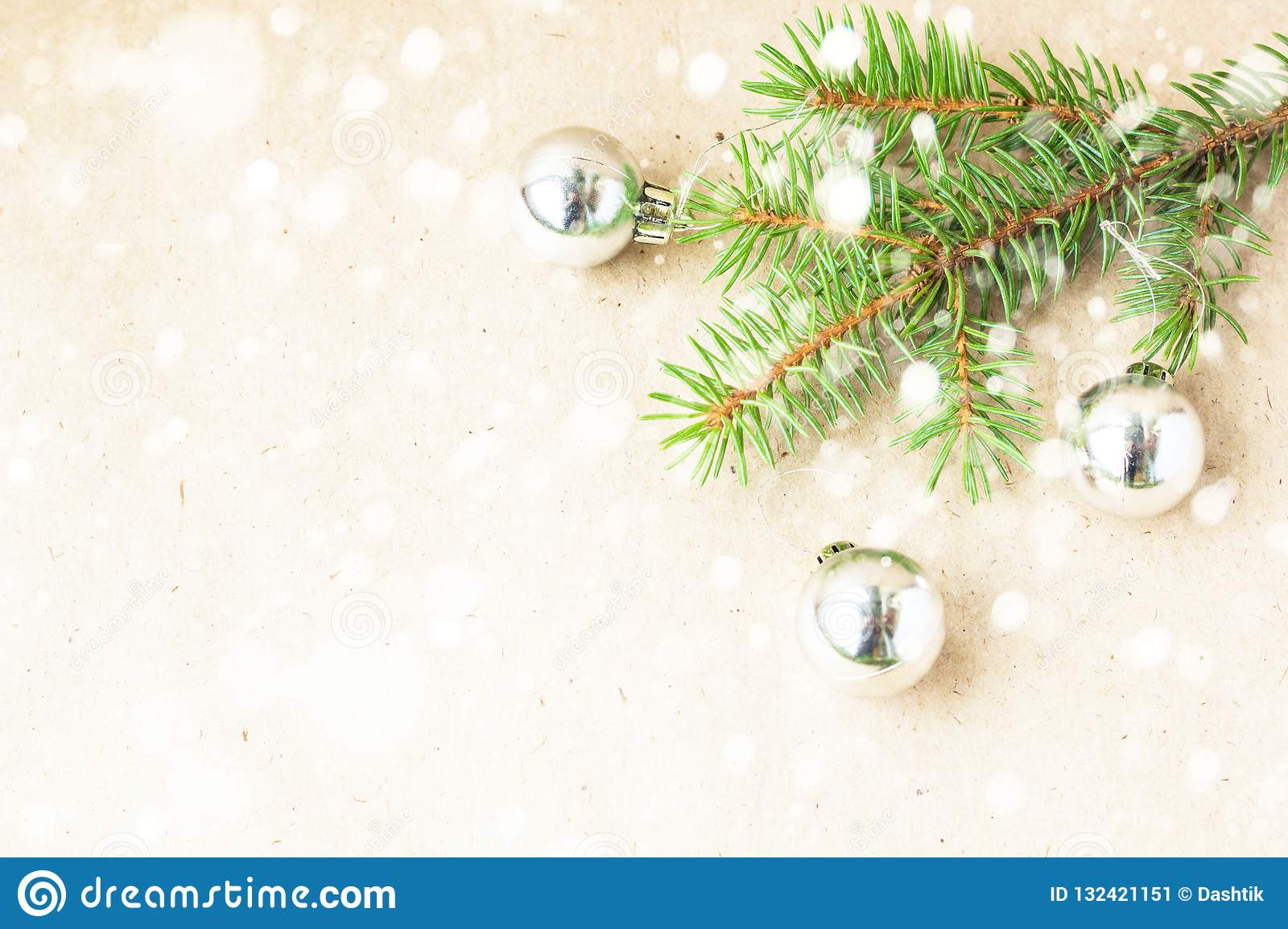 Fir tree branches decorated with silver christmas balls as border on a snow rustic holiday background frame