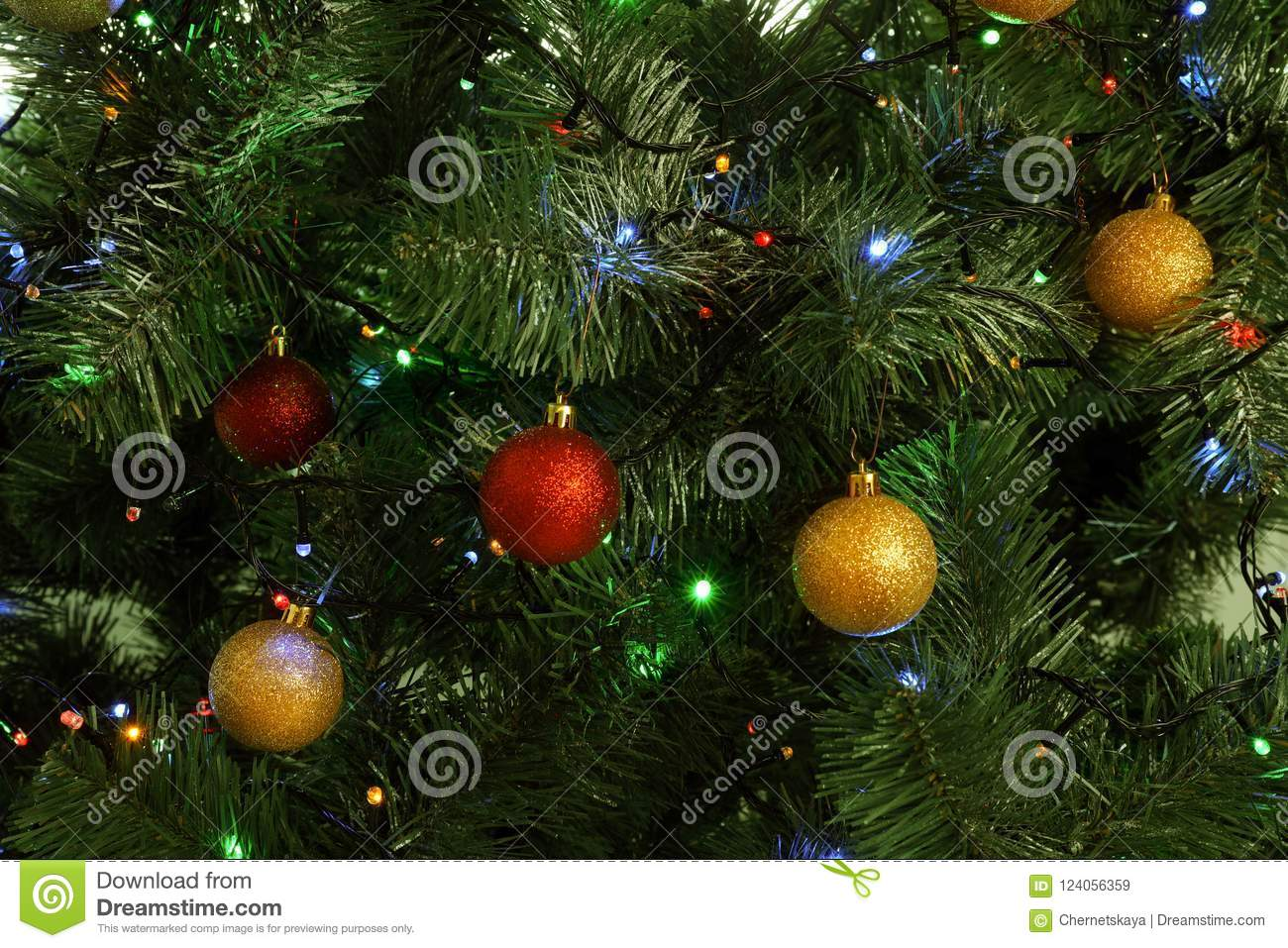 Fir tree with festive decor and glowing Christmas lights