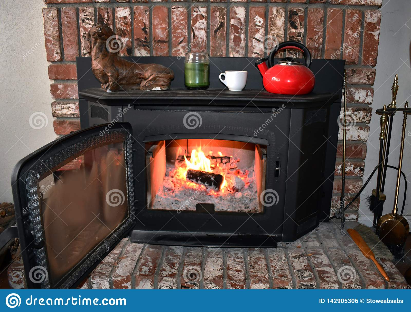 Fire in brick fireplace and mantle inside a cozy family room