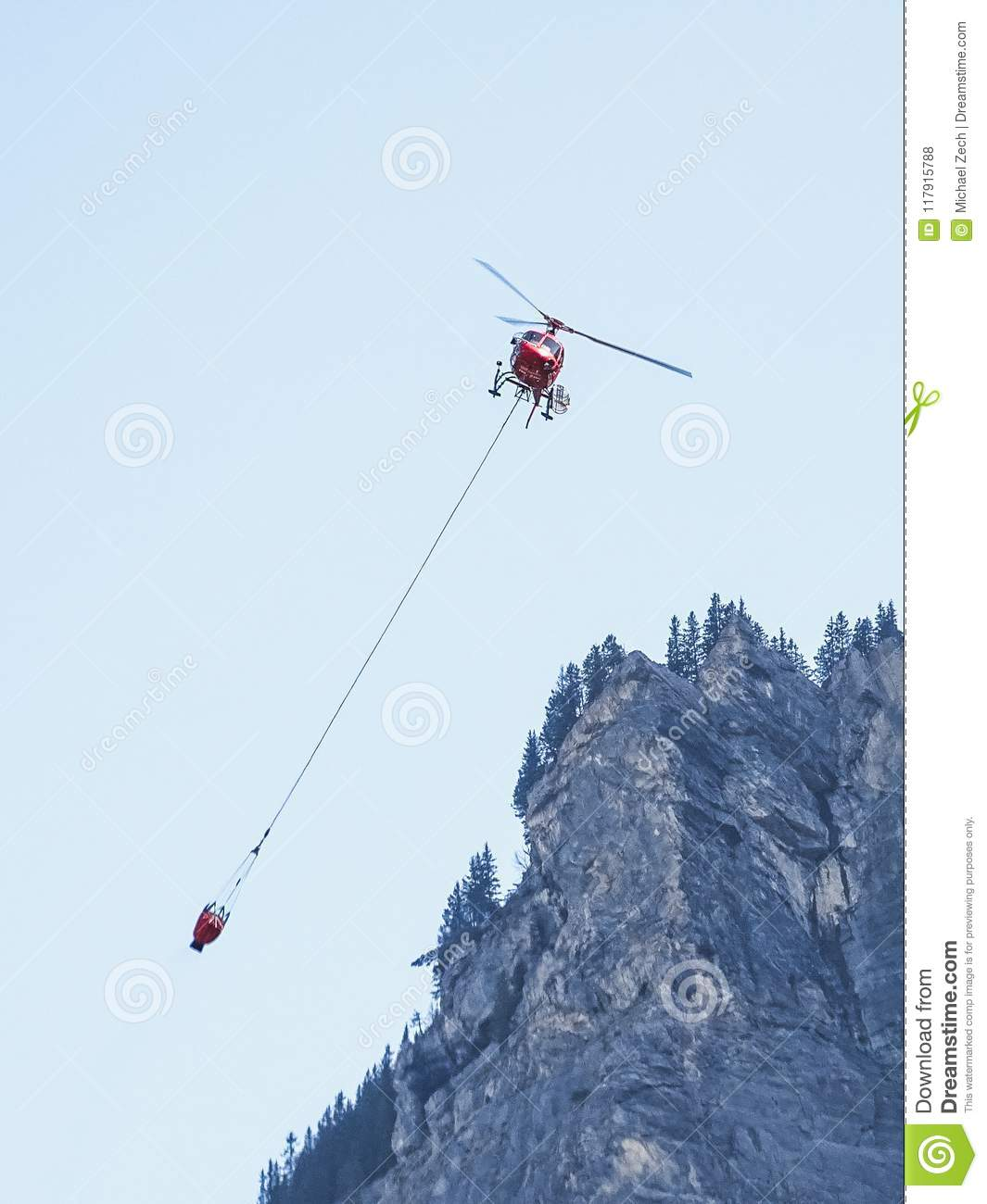 Fire helicopter with water tank in the air near kandersteg