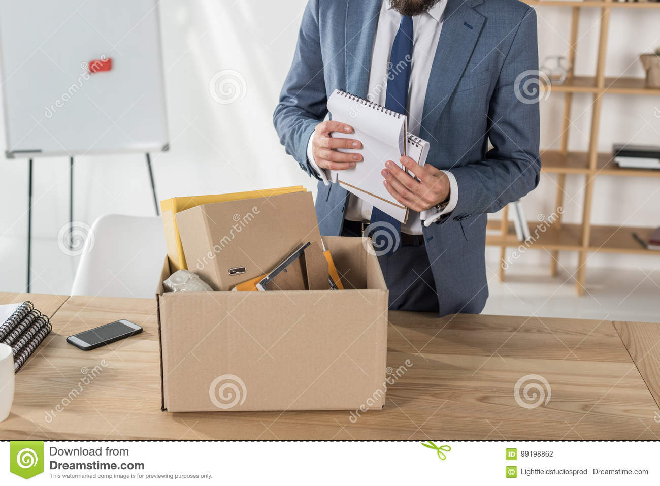 fired businessman packing office supplies in cardboard box at