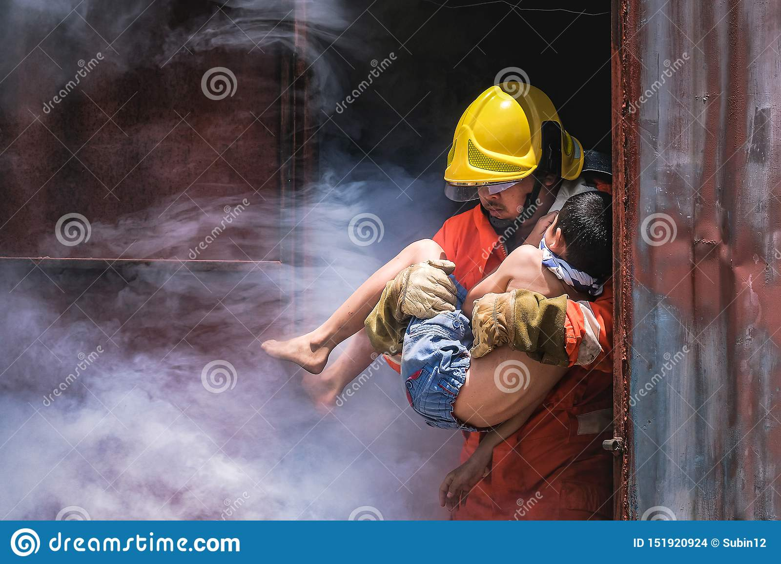 Firefighter holding child boy to save him in fire and smoke Firemen rescue the boys