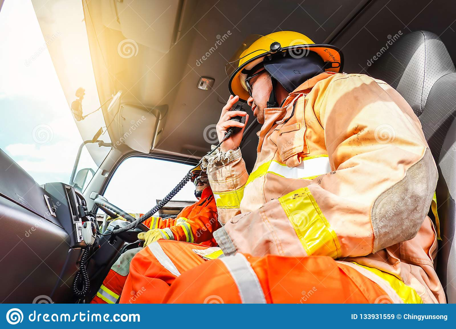 A firefighter in protective clothing and a helmet sits in a cargo rescue vehicle and talks on the radio