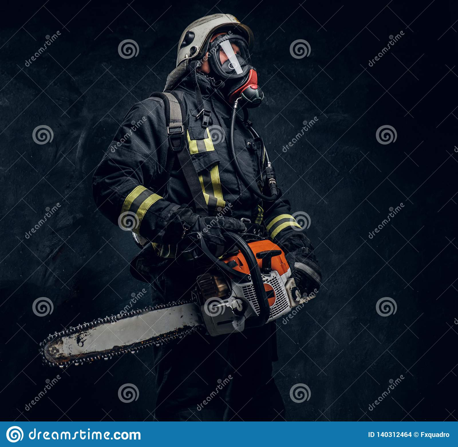 Portrait of a firefighter in safety helmet and oxygen mask holding a chainsaw. Studio photo against a dark textured wall