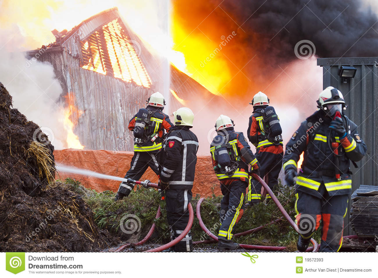 Group of firefighters in front of a dutch farm on fire.