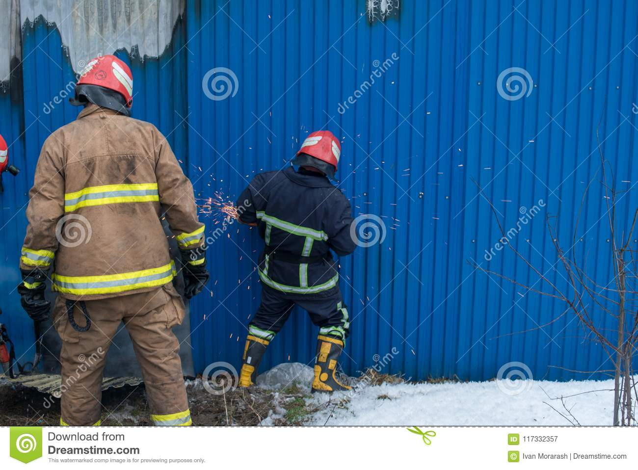 Firefighters Work On An Fire Of Building Using A Metal Cutter Rescue