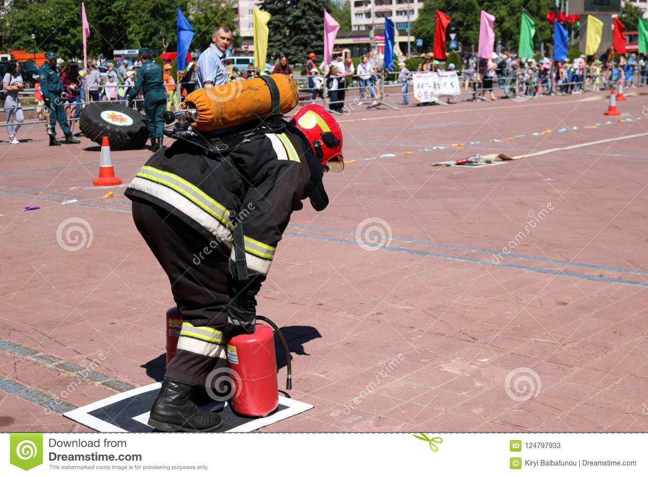 435b06c1a227 A fireman in a fireproof suit and a helmet running with red fire  extinguishers to extinguish a fire at a fire sport competition
