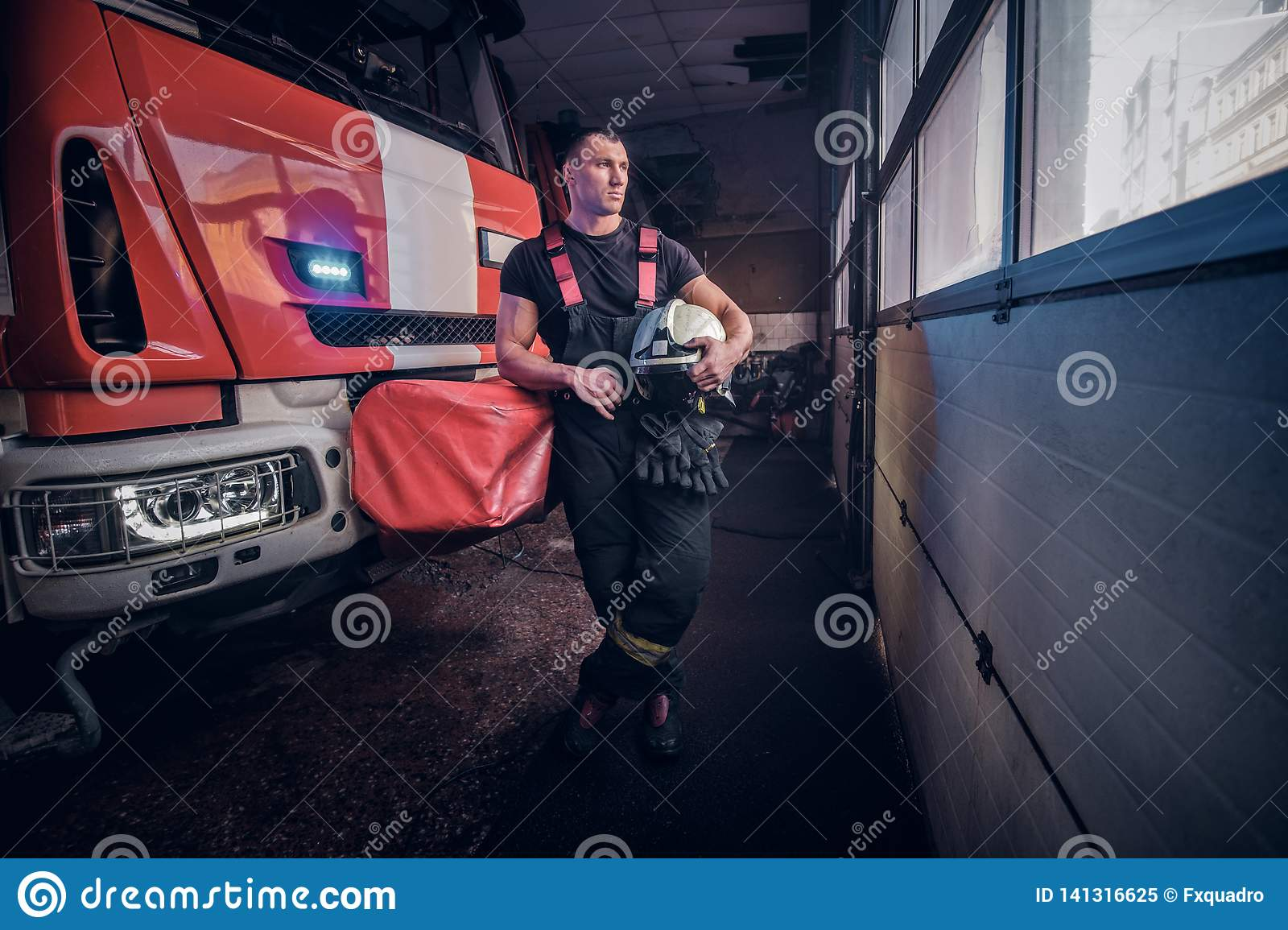 Young fireman holding a jacket and protective helmet in a garage of a fire department, leaning on a fire engine and