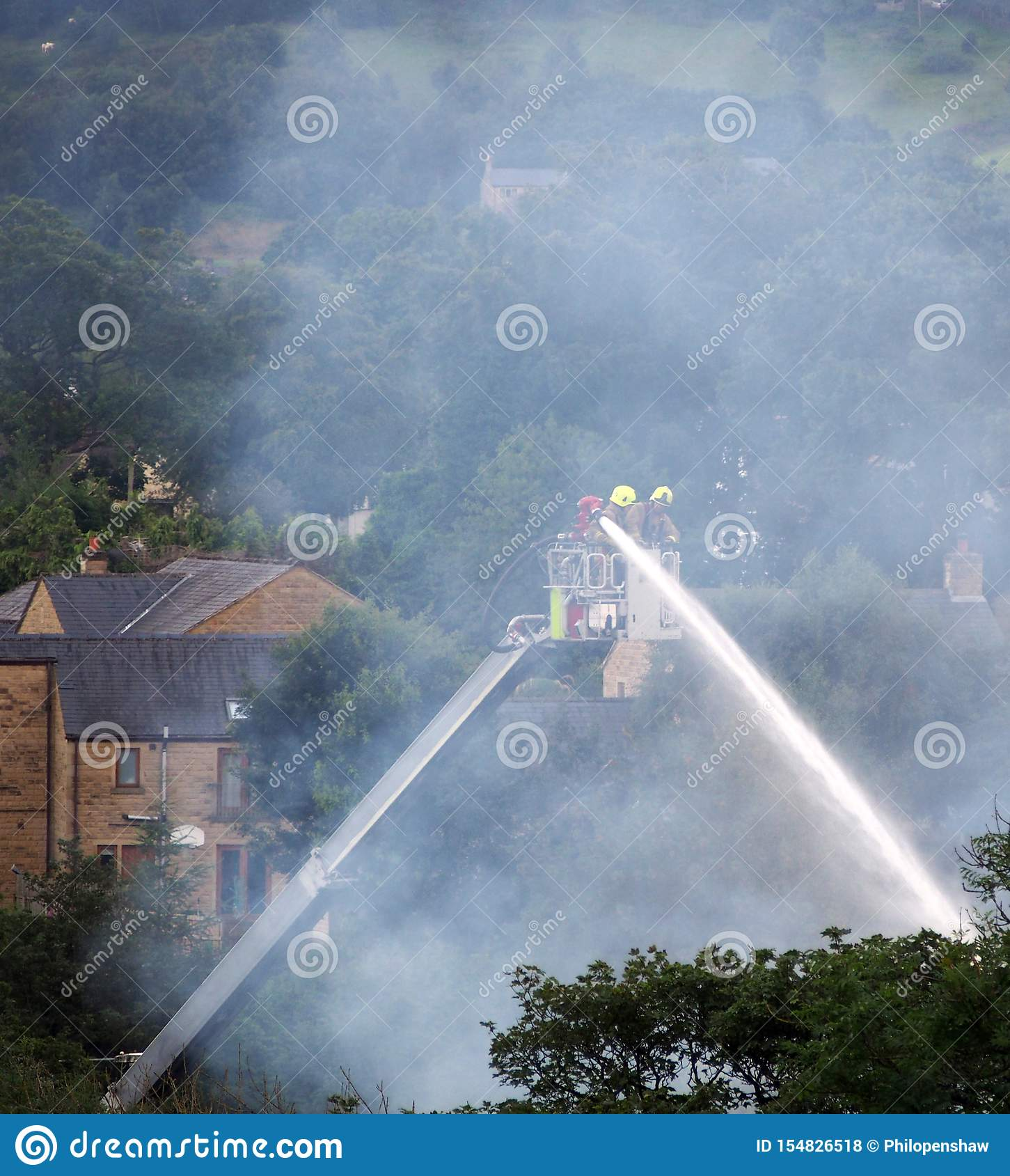 Firemen on an elevated platform putting out the fire at the former walkeys clogs mill in hebden bridge